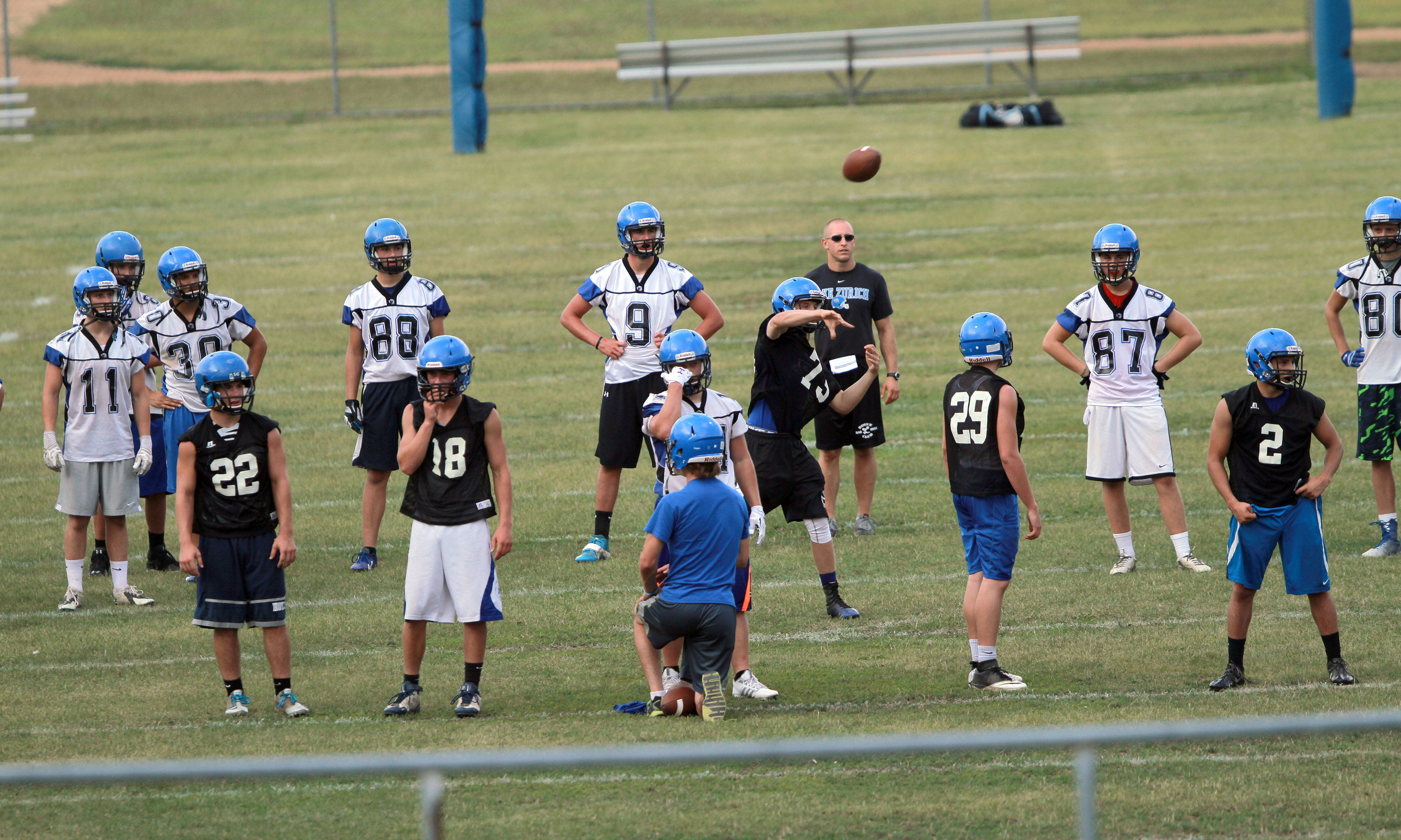 Players go through drills during football practice Monday at Lake Zurich High School.