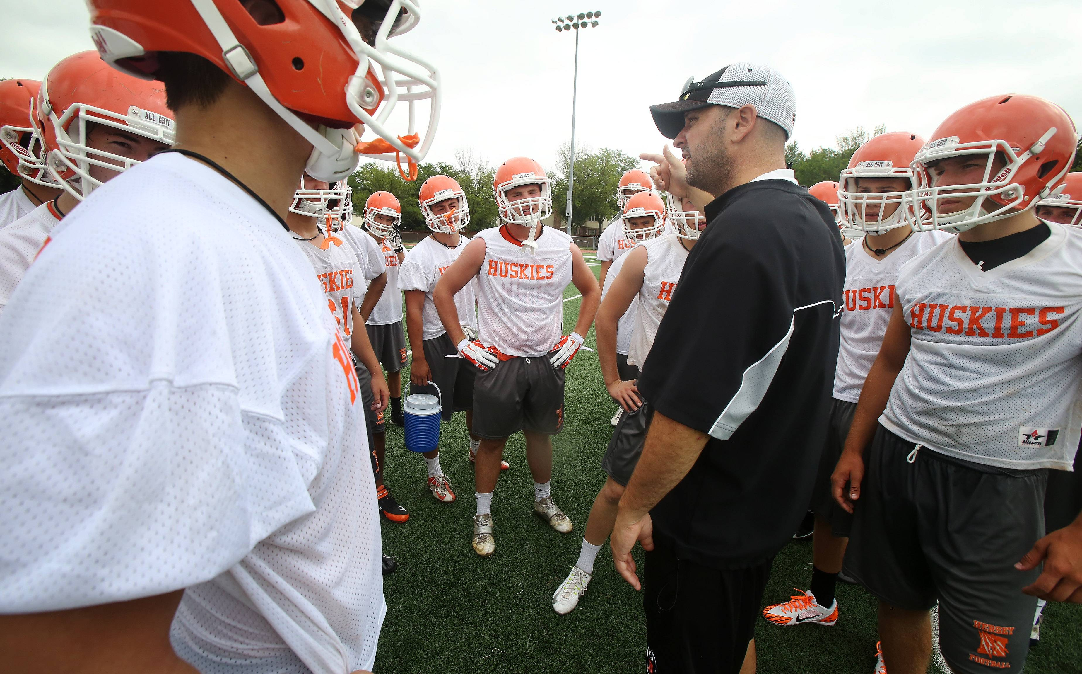 Football coach Joe Pardun talks to his team during drills on the first day of football practice at Hersey High School on Monday. Pardun is starting his first year leading the team after several years as an assistant.