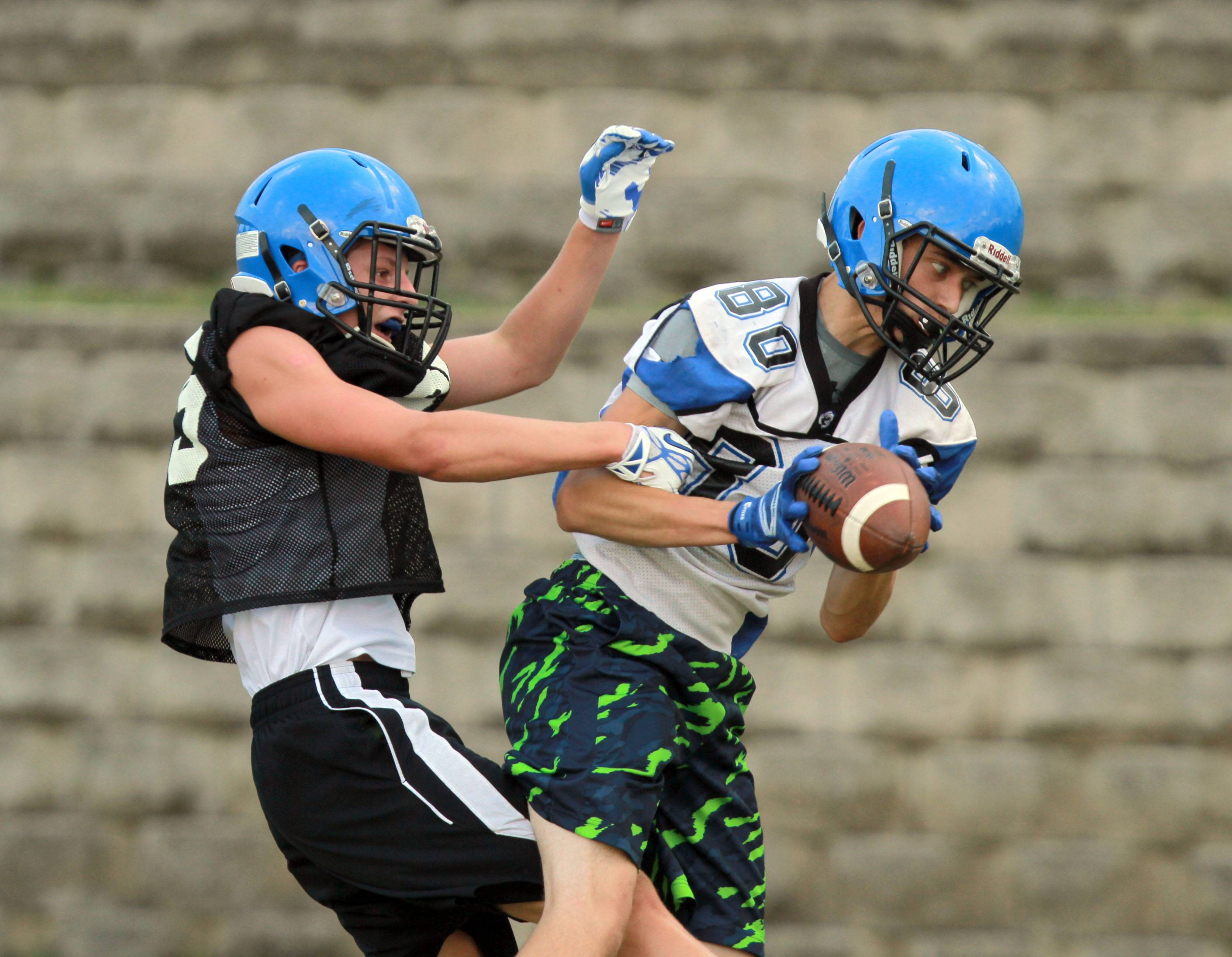 DJ Smith, right, and Matt Lawson go up for a pass during football practice Monday at Lake Zurich High School.