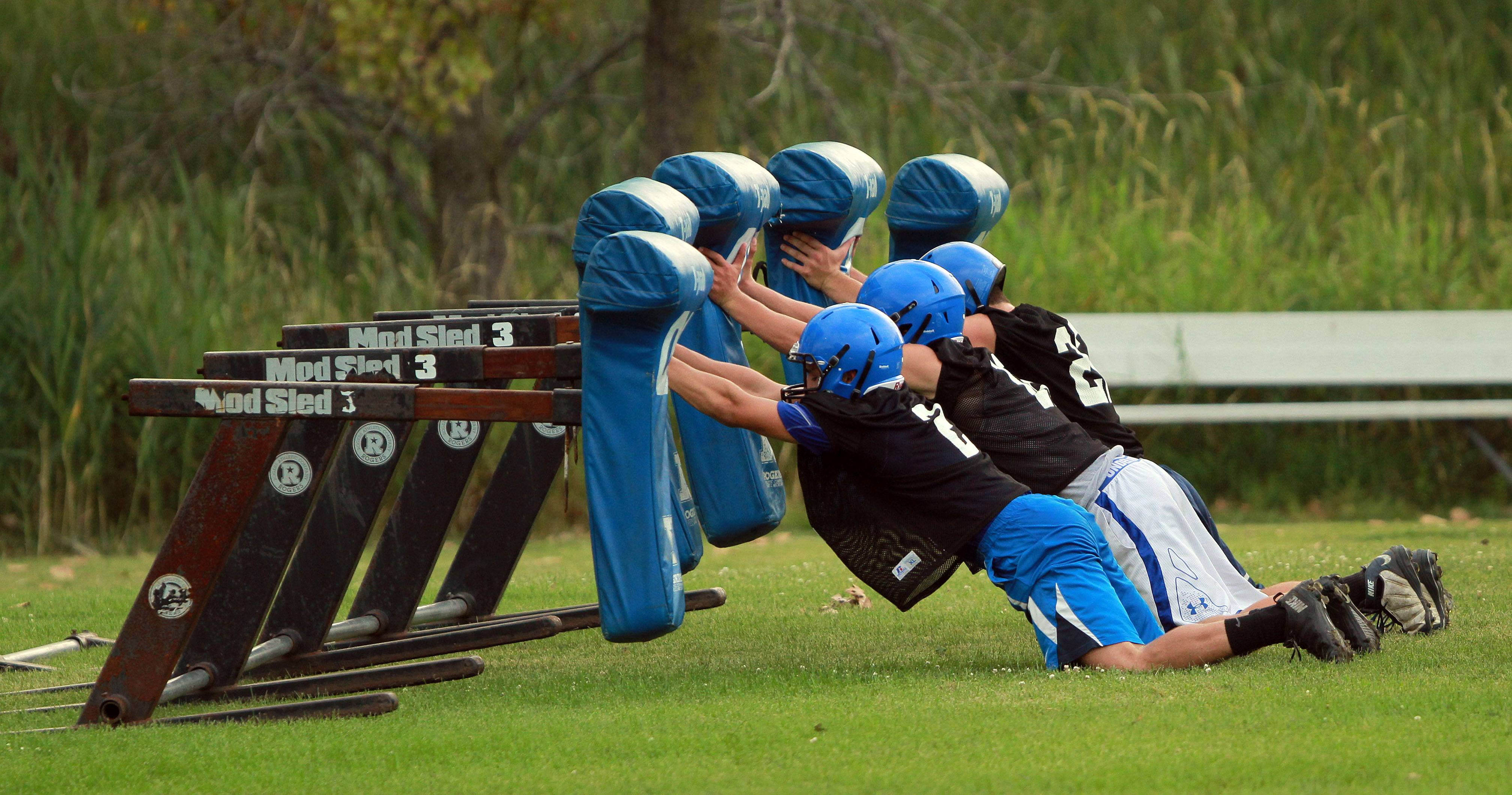 Defensive players go through drills during football practice Monday at Lake Zurich High School.