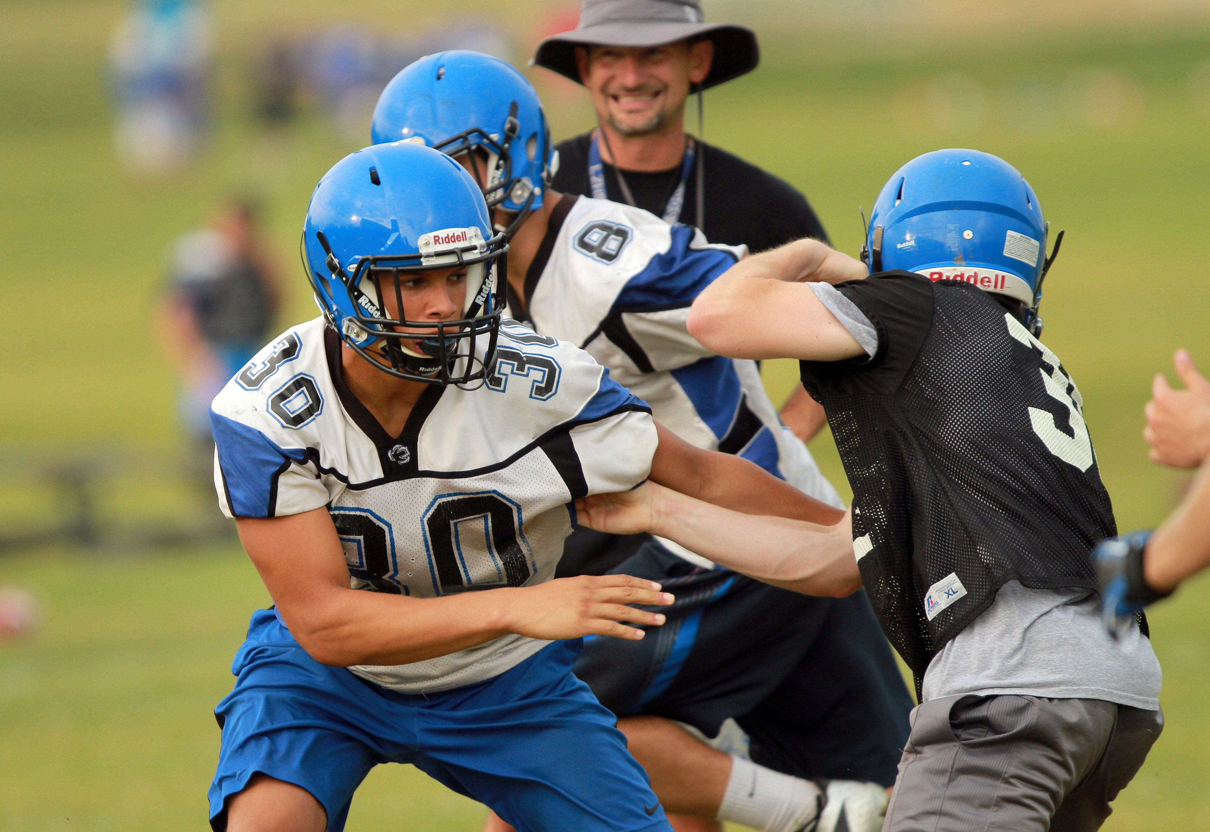 Ben Klett blocks during football practice Monday at Lake Zurich High School.