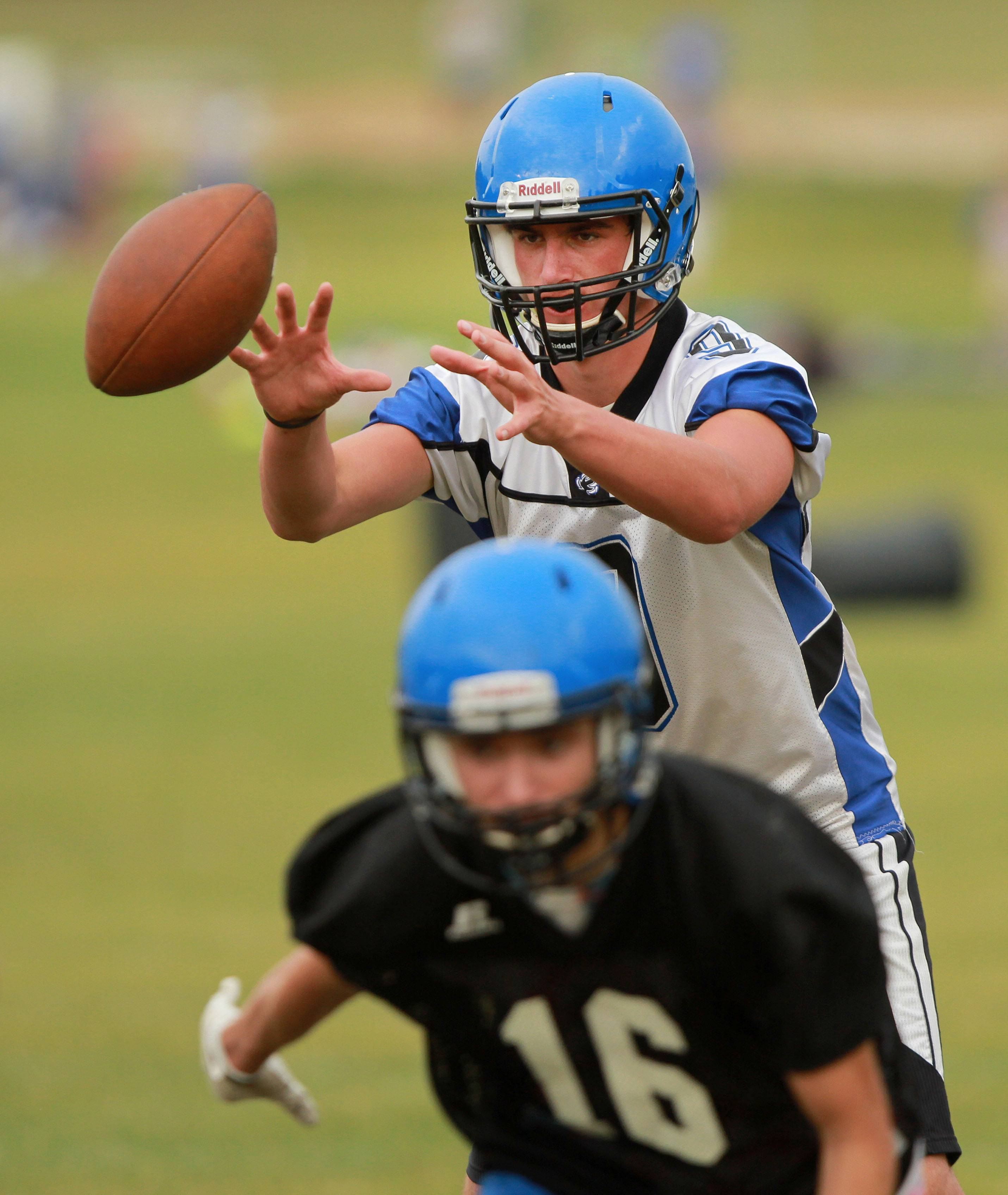 Quarterback Joey Lindstrom receives a snap during football practice Monday at Lake Zurich High School.