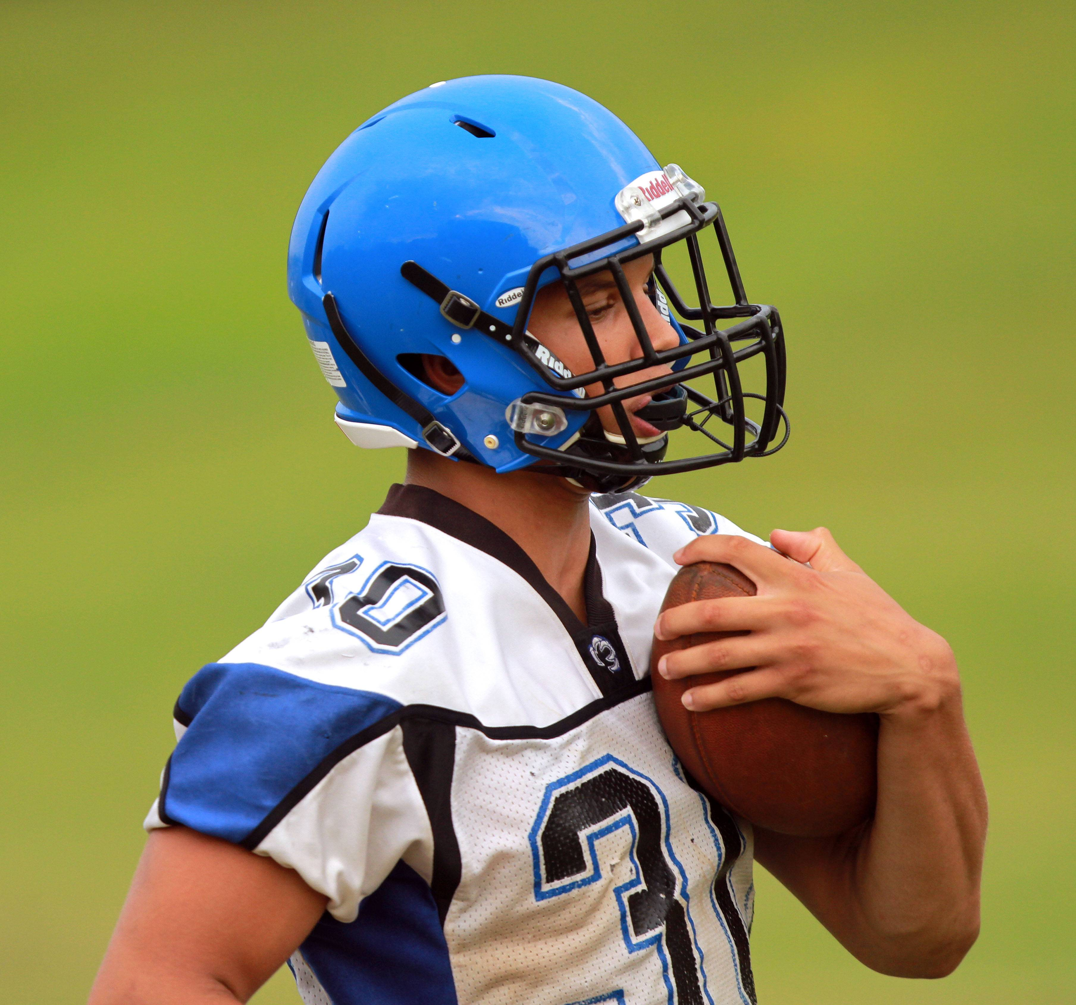 Ben Klett runs with the ball during football practice Monday at Lake Zurich High School.