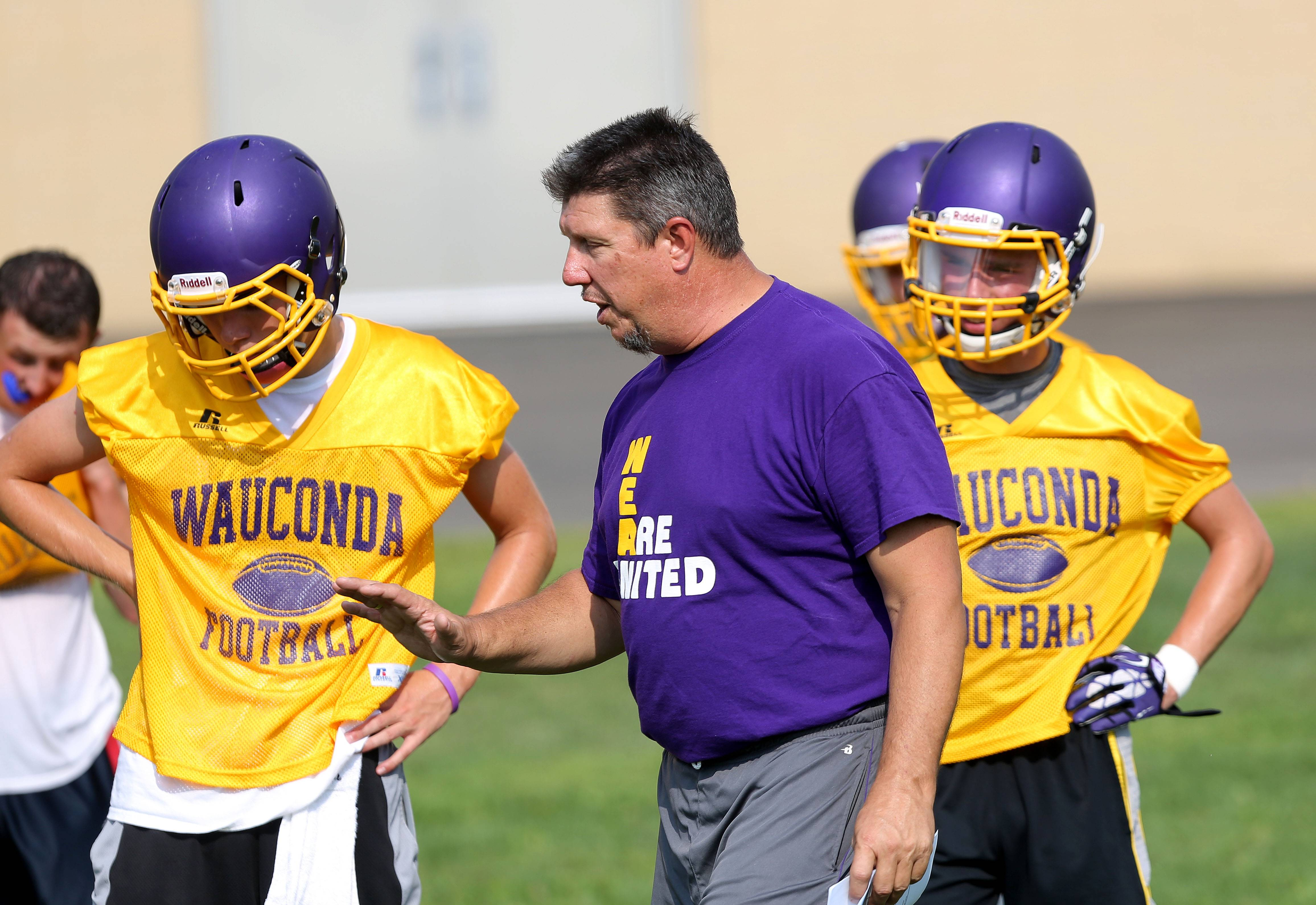 Head coach Dave Mills talks to players during football practice Monday at Wauconda High School.