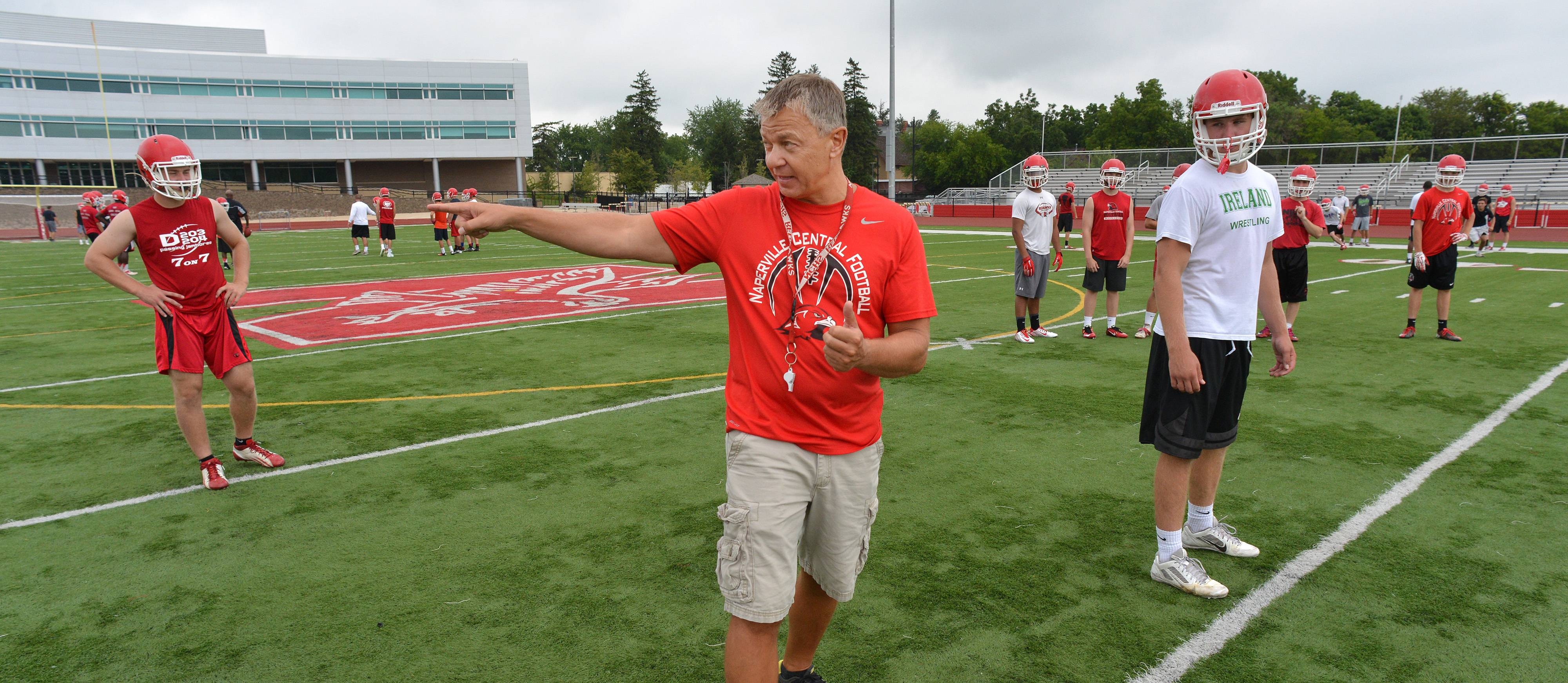 Naperville Central High School's football team works Monday out on the first official day of practice. Head coach Mike Stine shows where players are to set up.