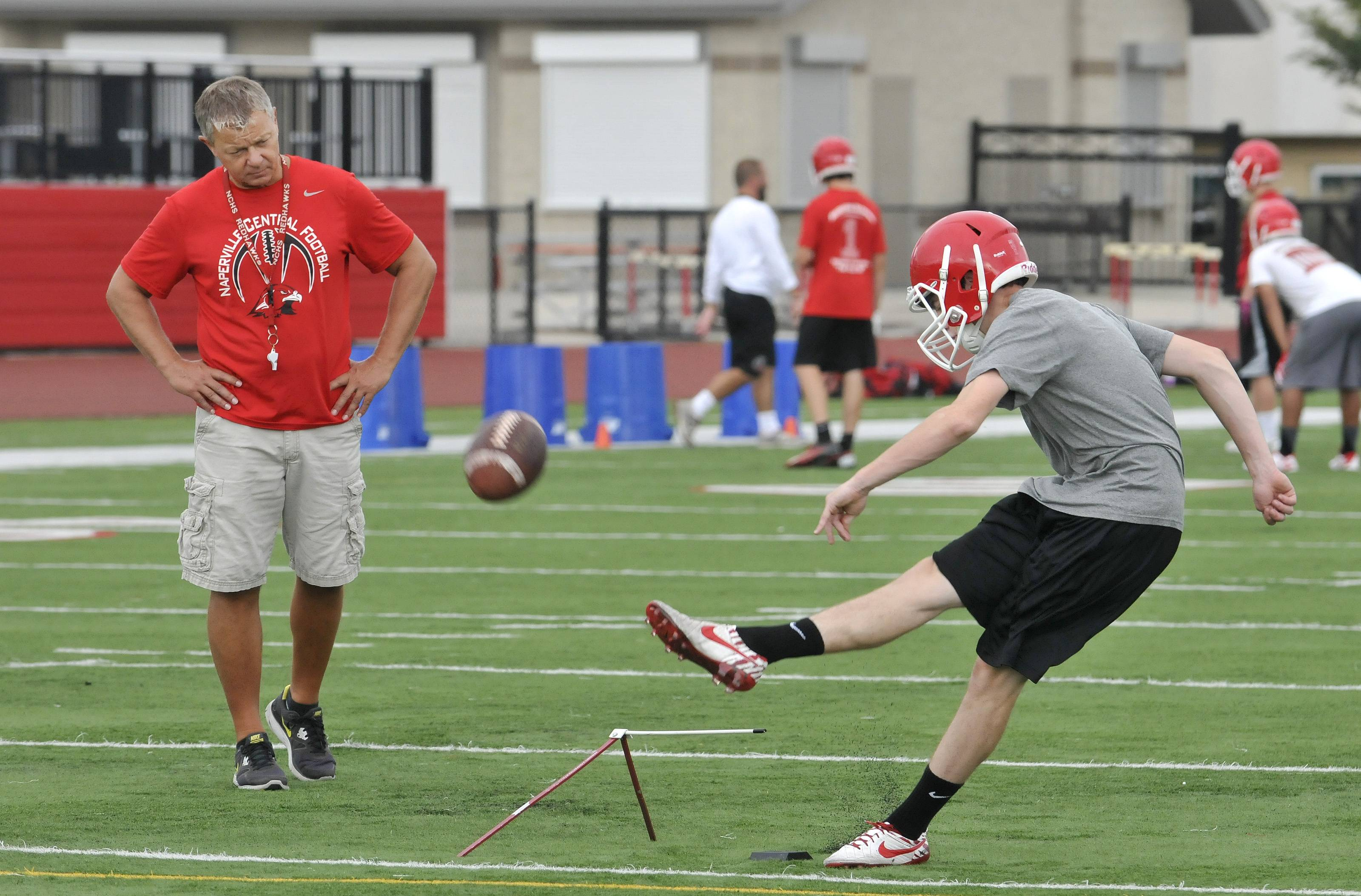Naperville Central High School's football team works Monday out on the first official day of practice. Head coach Mike Stine watches kicker Connor Assalley practice field goals.