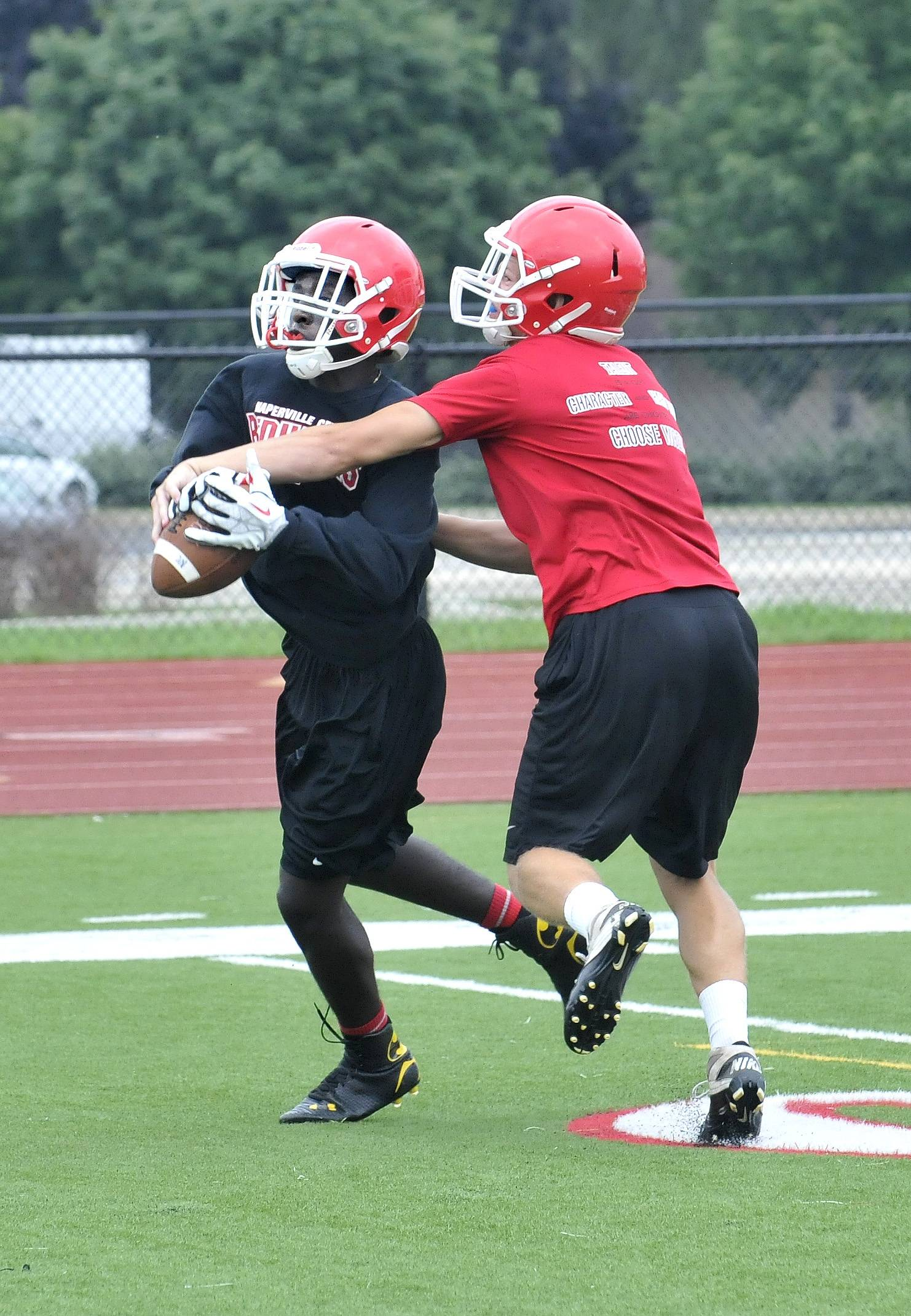 Naperville Central High School's Wide Receiver Emannuel Rugamba, left, pulls in a pass Monday.