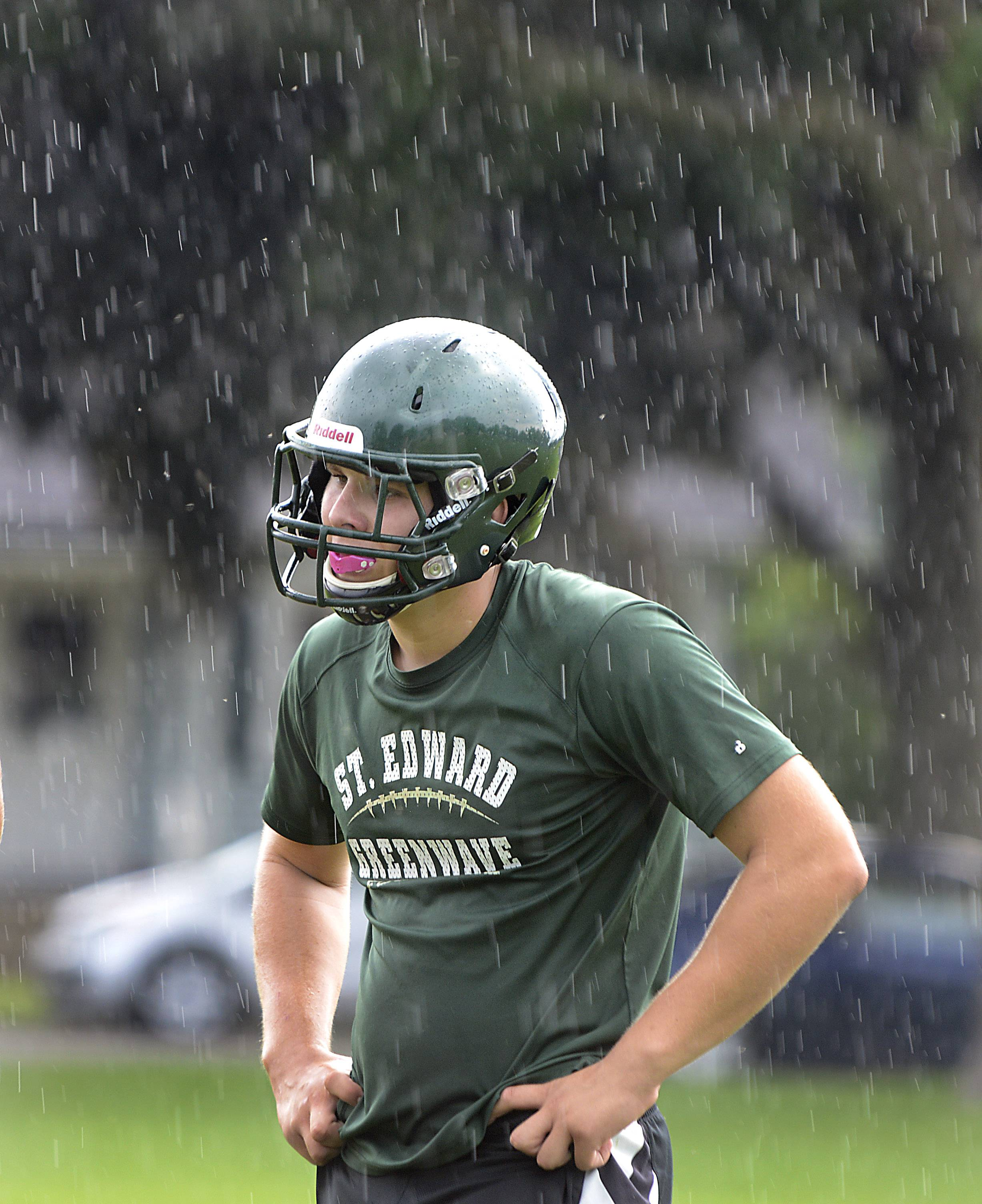 Brandon Ostrander stands in the cooling rain during St. Edward High School football practice Monday in Elgin.