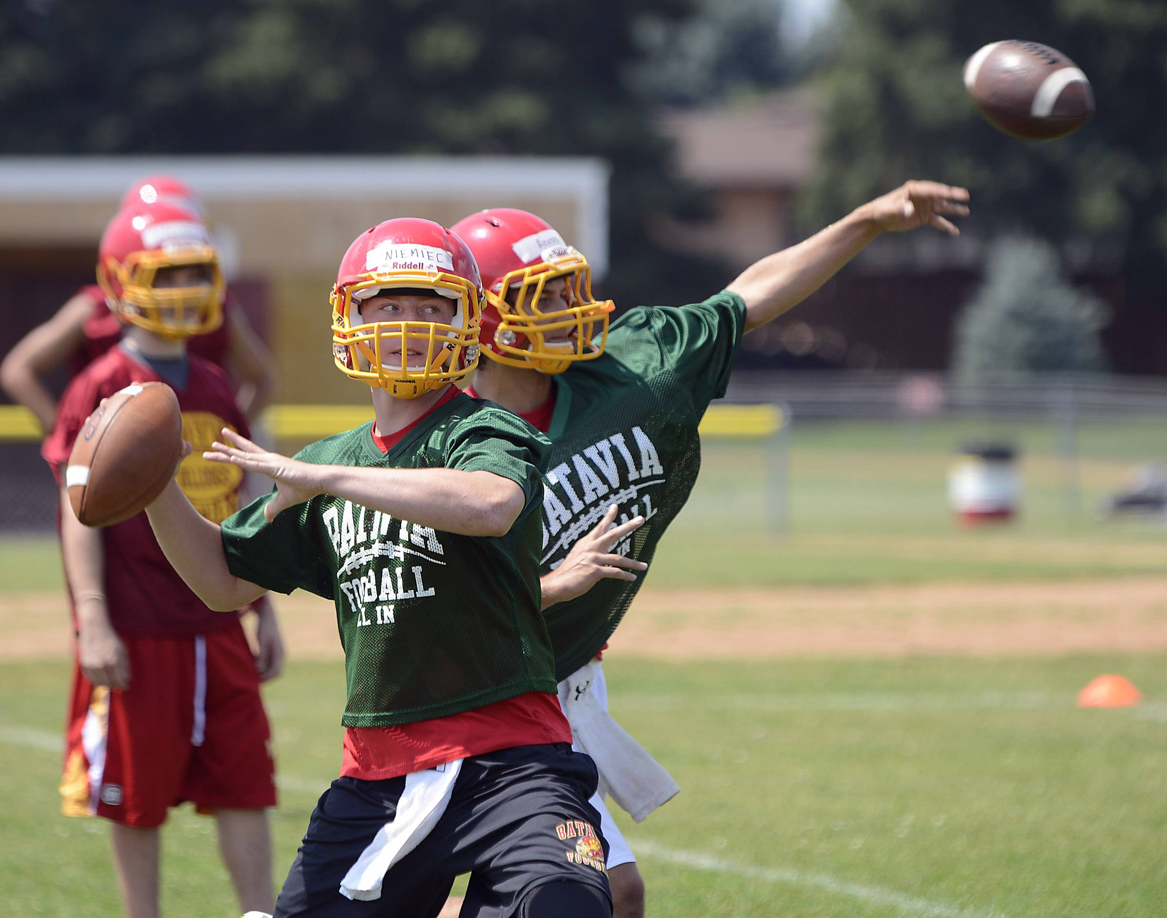 Quarterbacks Evan Acosta, right, and Kyle Niemiec, throw during Batavia High School football practice Monday.