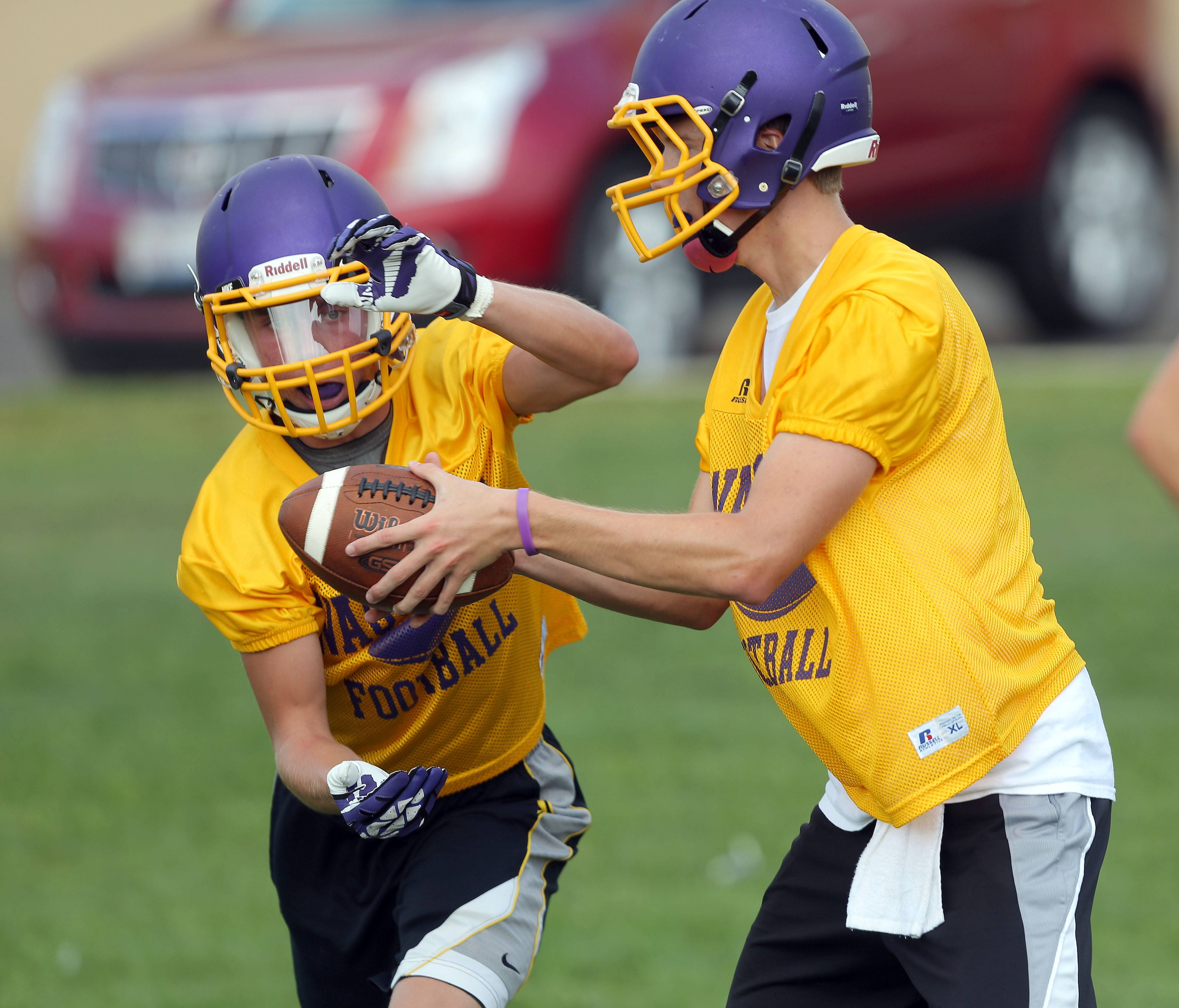 Quarterback Kevin Malisheski, right, hands off to running back Tyler Theel during football practice Monday at Wauconda.