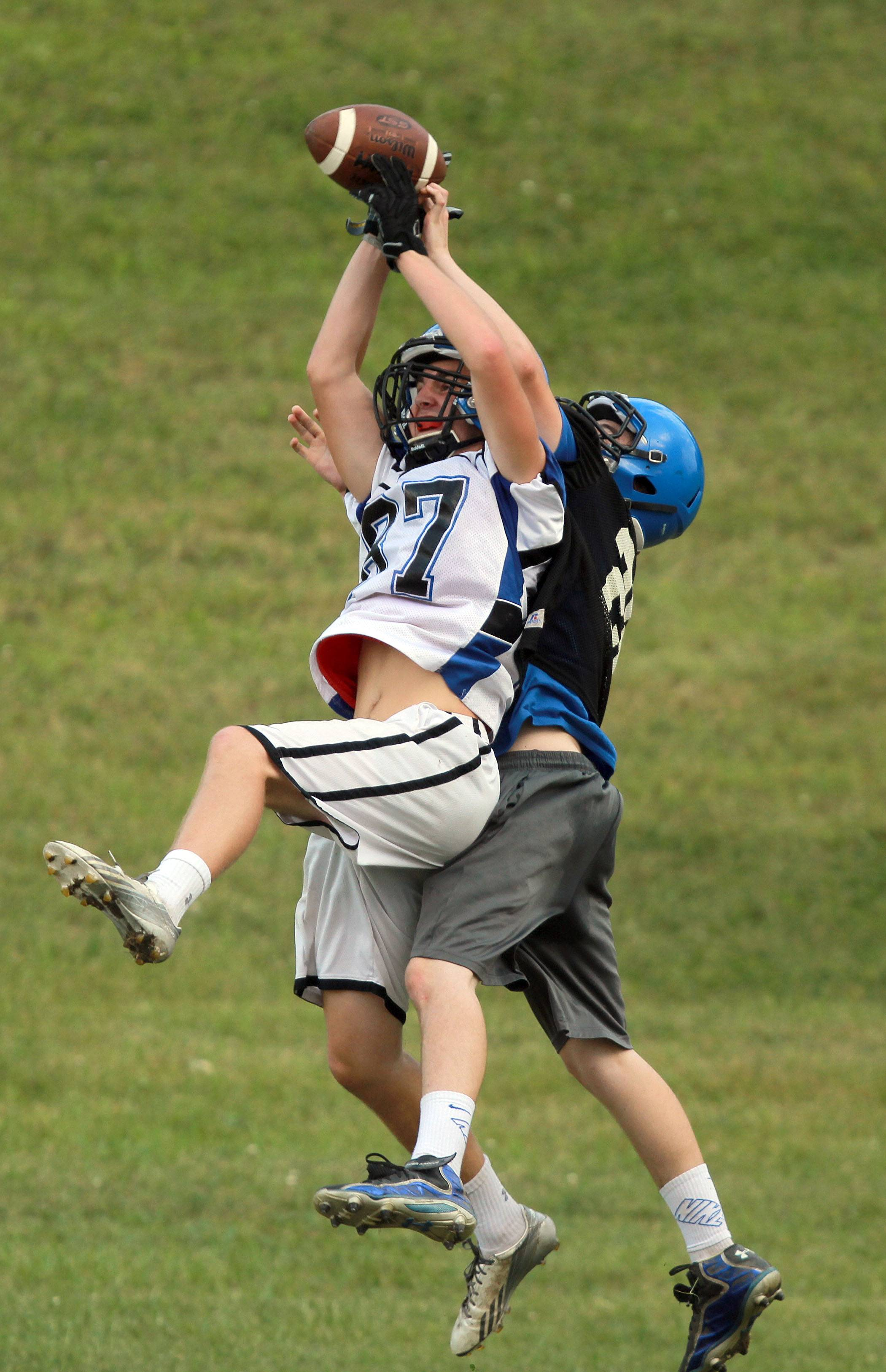 Steve Lundy/slundy@dailyherald.comPat Rigby, left, goes up for a pass with Jeremy Brown during football practice Monday at Lake Zurich.