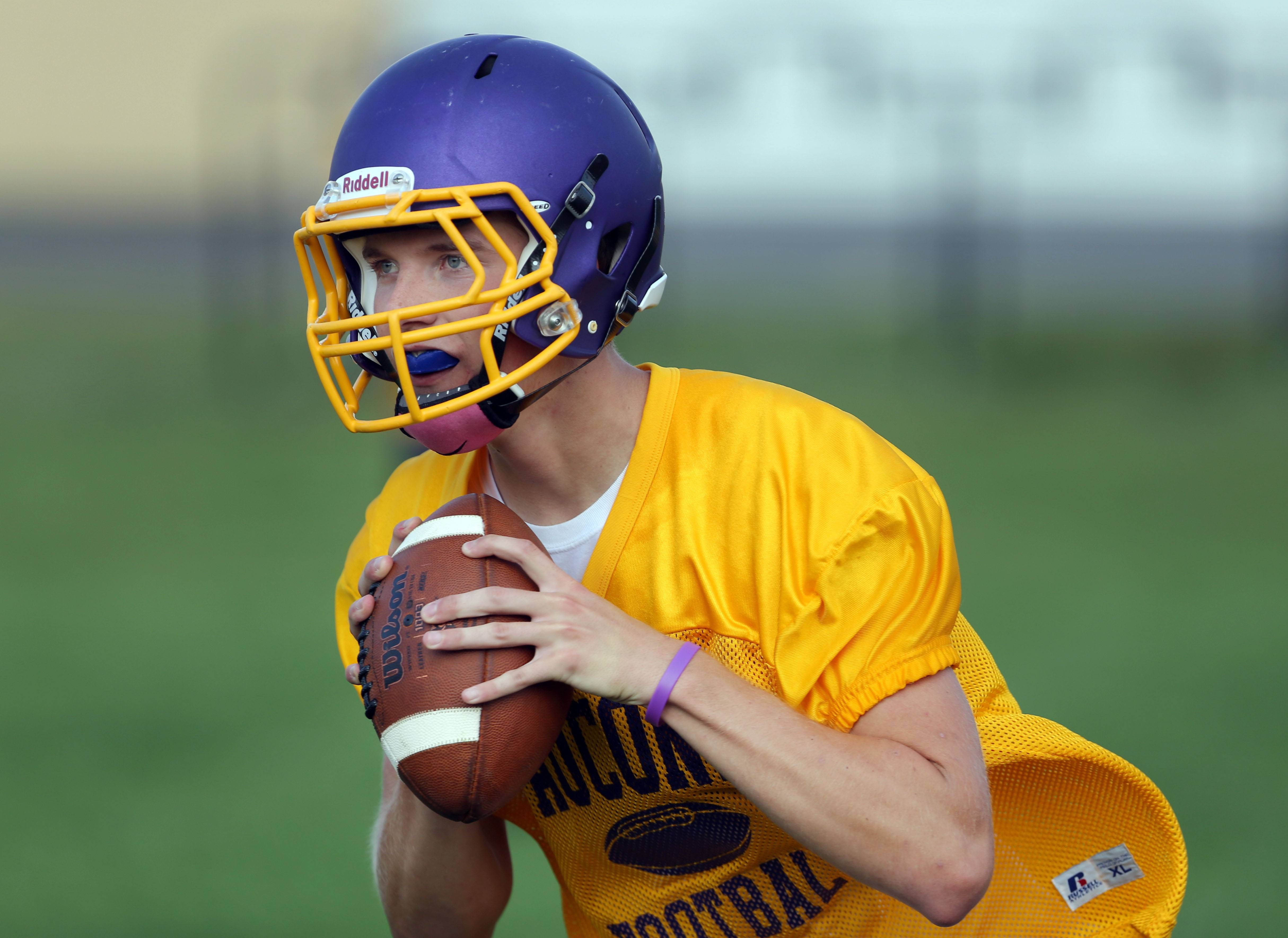 Quarterback Kevin Malisheski rolls out during football practice Monday at Wauconda.
