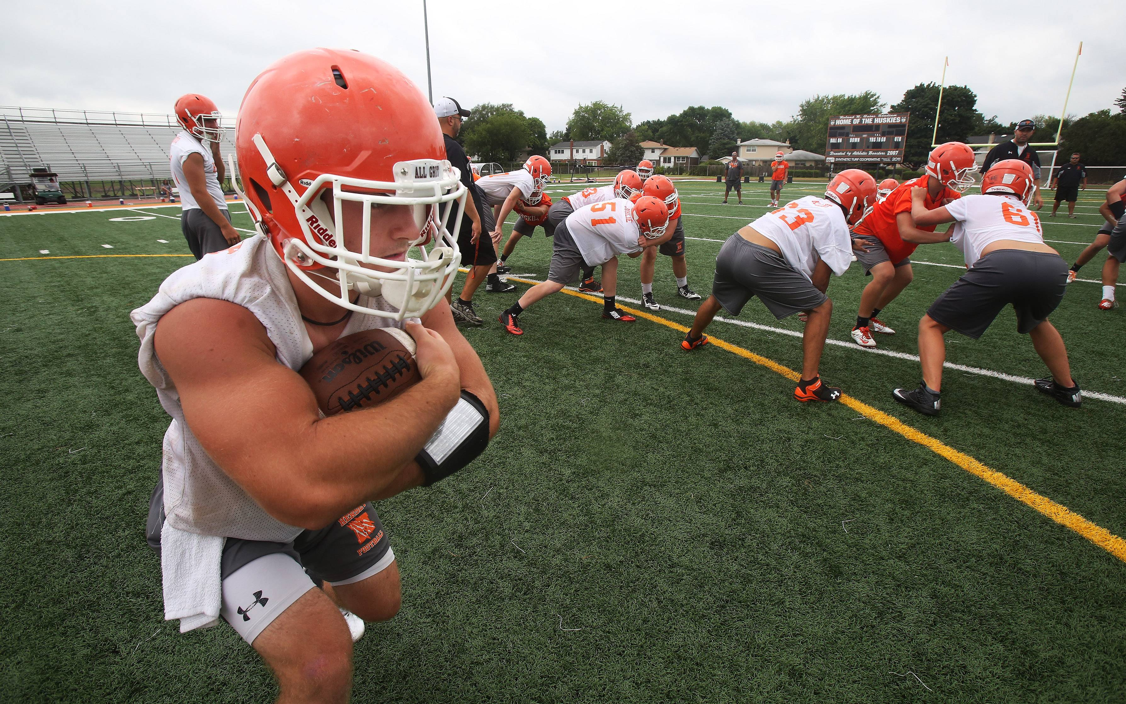 Running back Chase Bandolik carries the ball during the first day of football practice at Hersey on Monday.