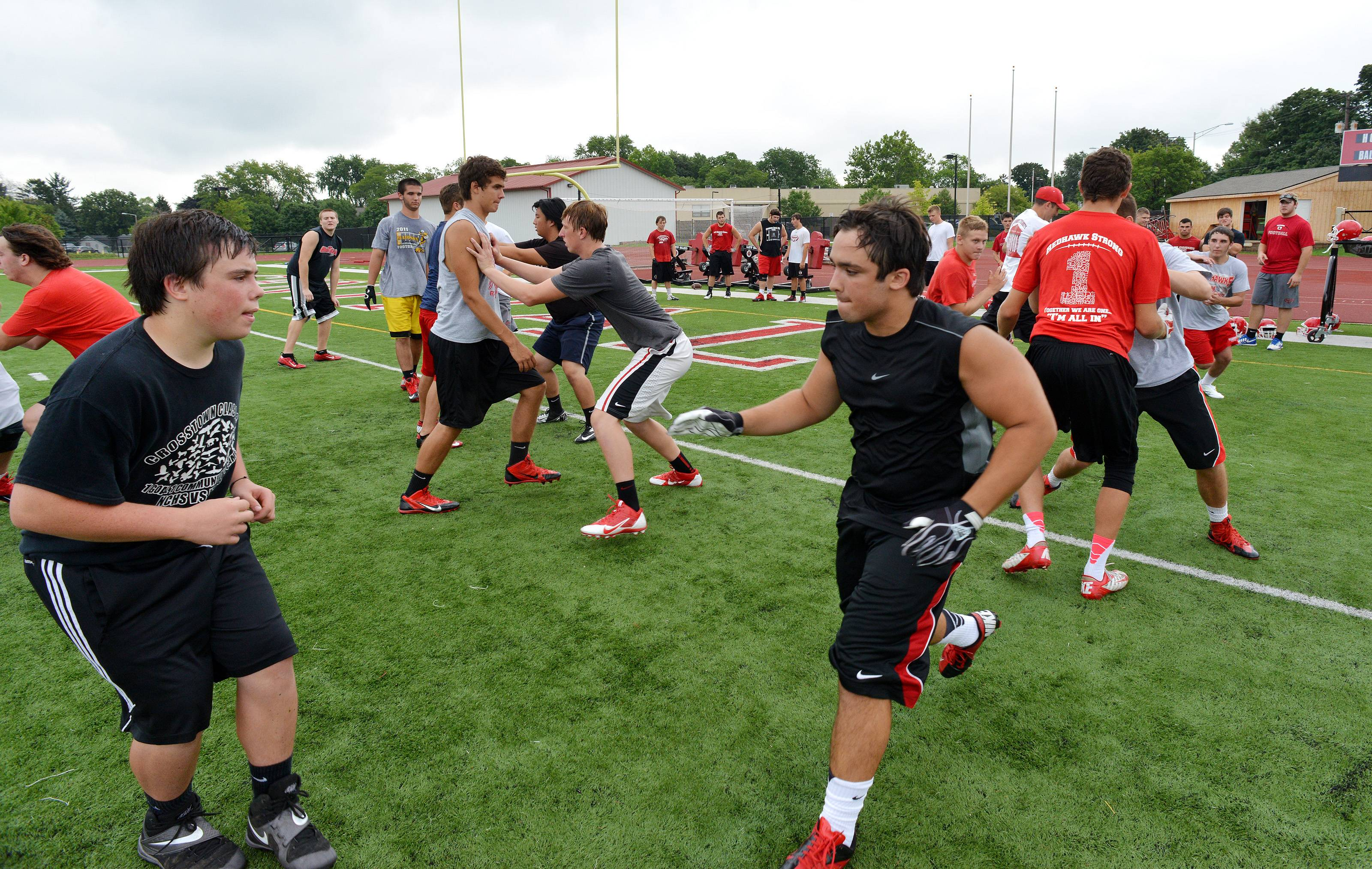 Naperville Central High School's football team works Monday out on the first official day of practice. Linemen face off against each other in drills.