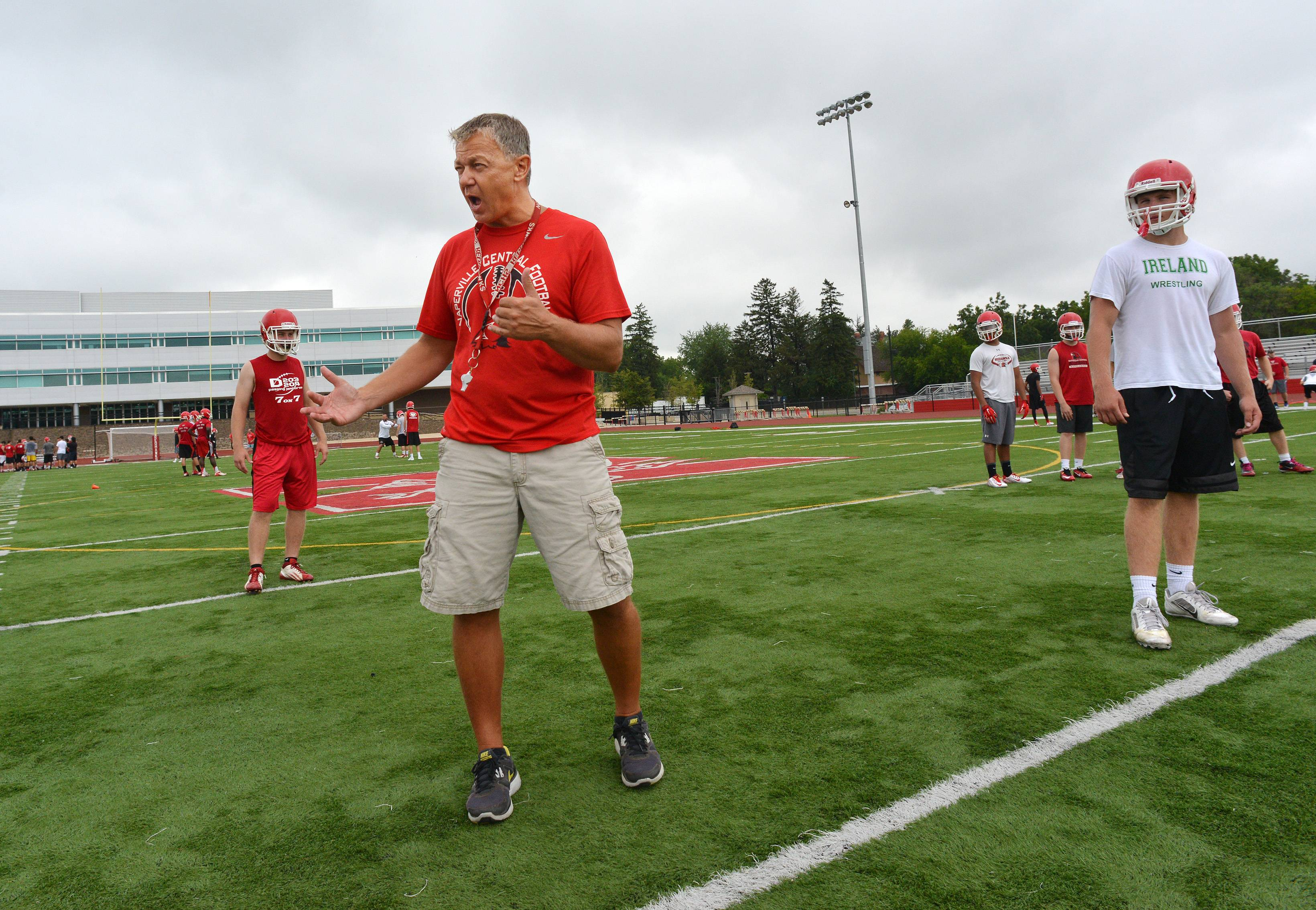 Naperville Central High School's football team works Monday out on the first official day of practice. Mike Stine shows where players are to set up.