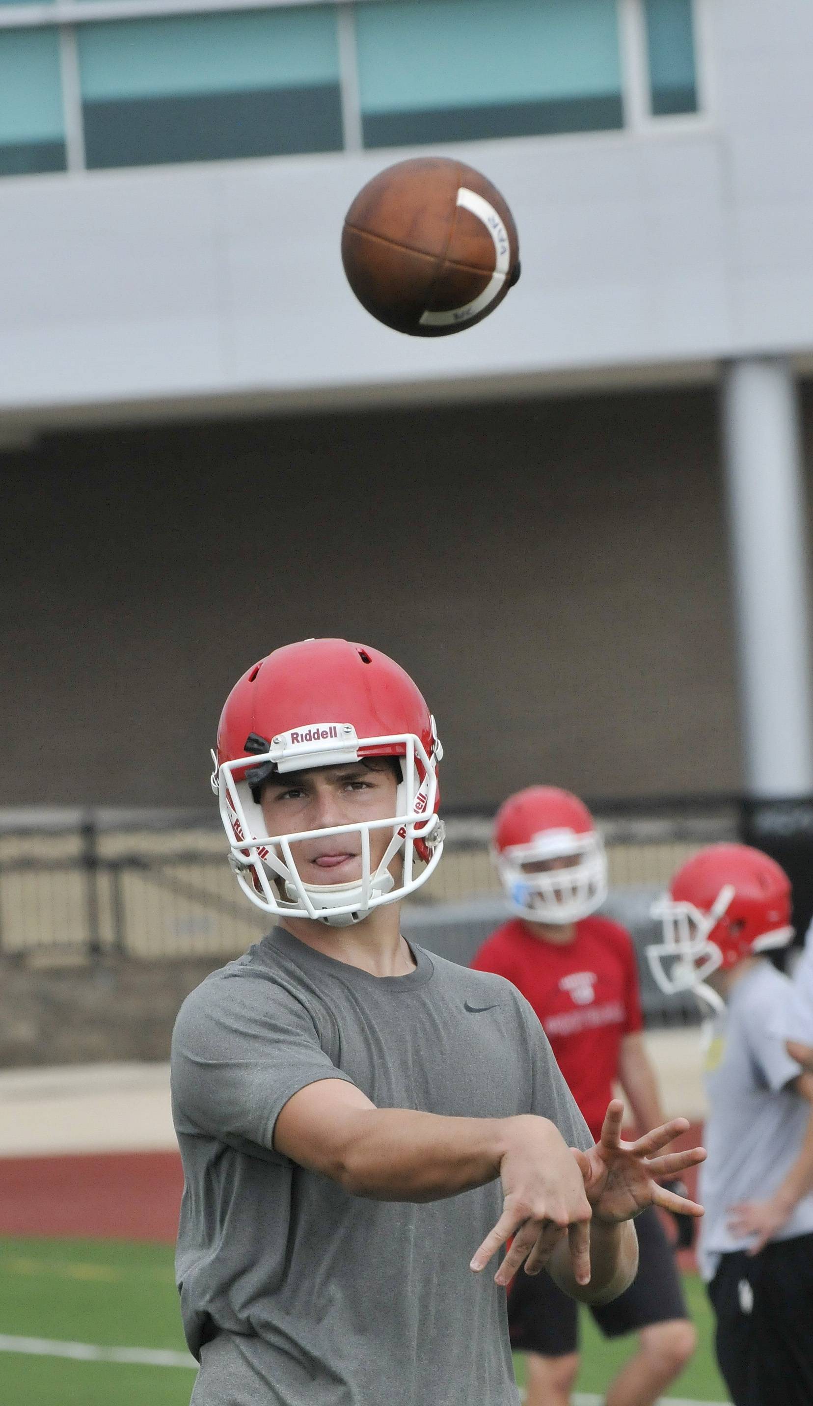 Naperville Central High School's football team works Monday out on the first official day of practice. Right-handed starting Quarterback Connor Joyce warms up with some practice tosses.