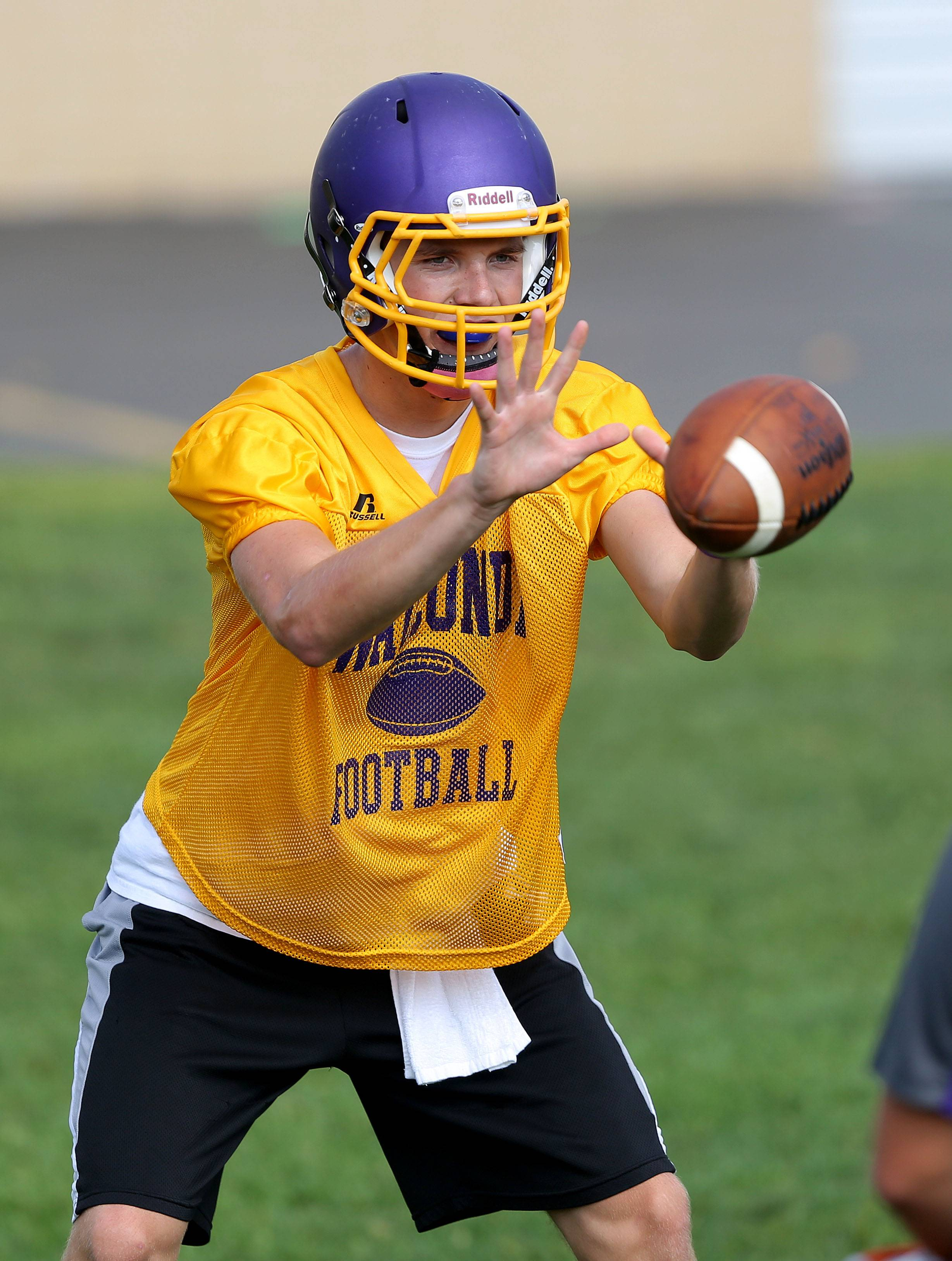QB Kevin Malisheski receives a snap during football practice Monday at Wauconda High School.