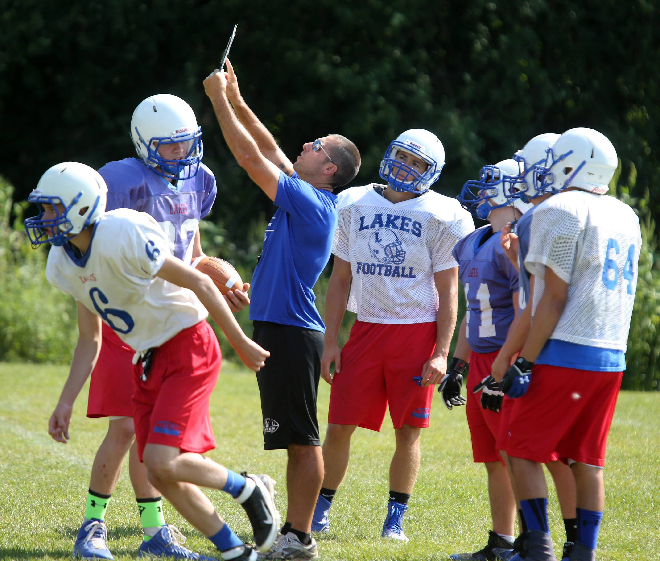 Lakes head varsity football coach Luke Mertens goes over a kicking play during practice on Friday in Lake Villa.