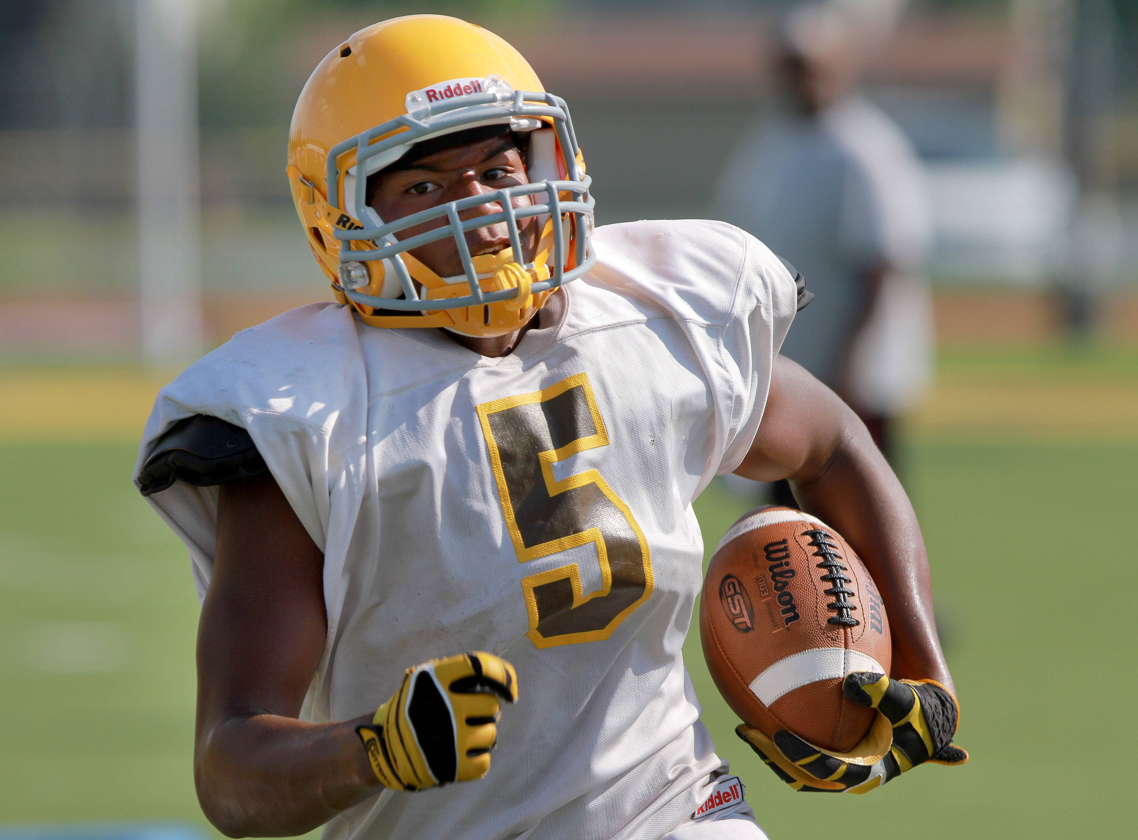 RB Zavier Barnes runs with the ball during football practice Tuesday at Carmel High School in Mundelein.
