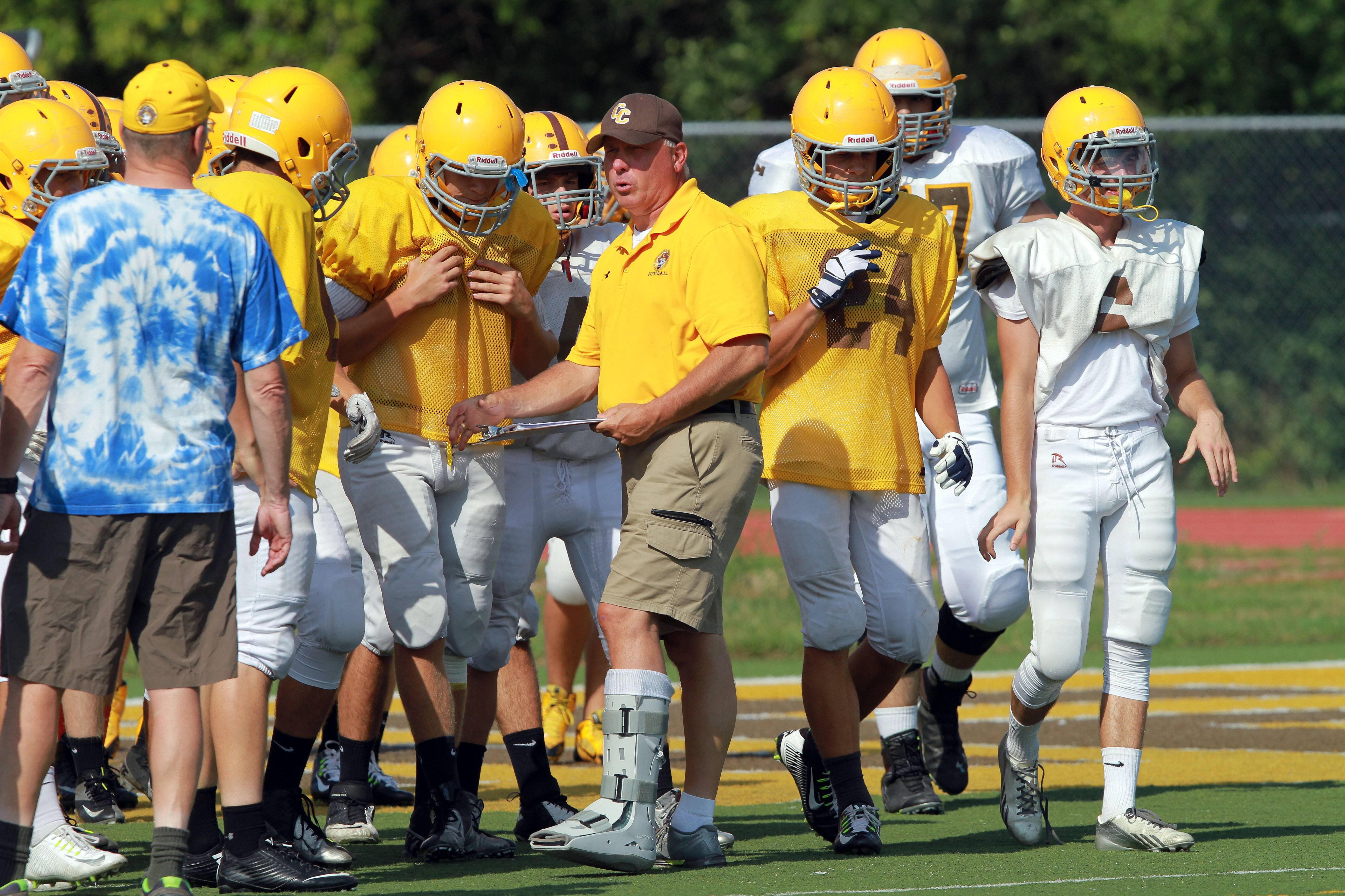 Head coach Andy Bitto talks with players during football practice Tuesday at Carmel High School in Mundelein.