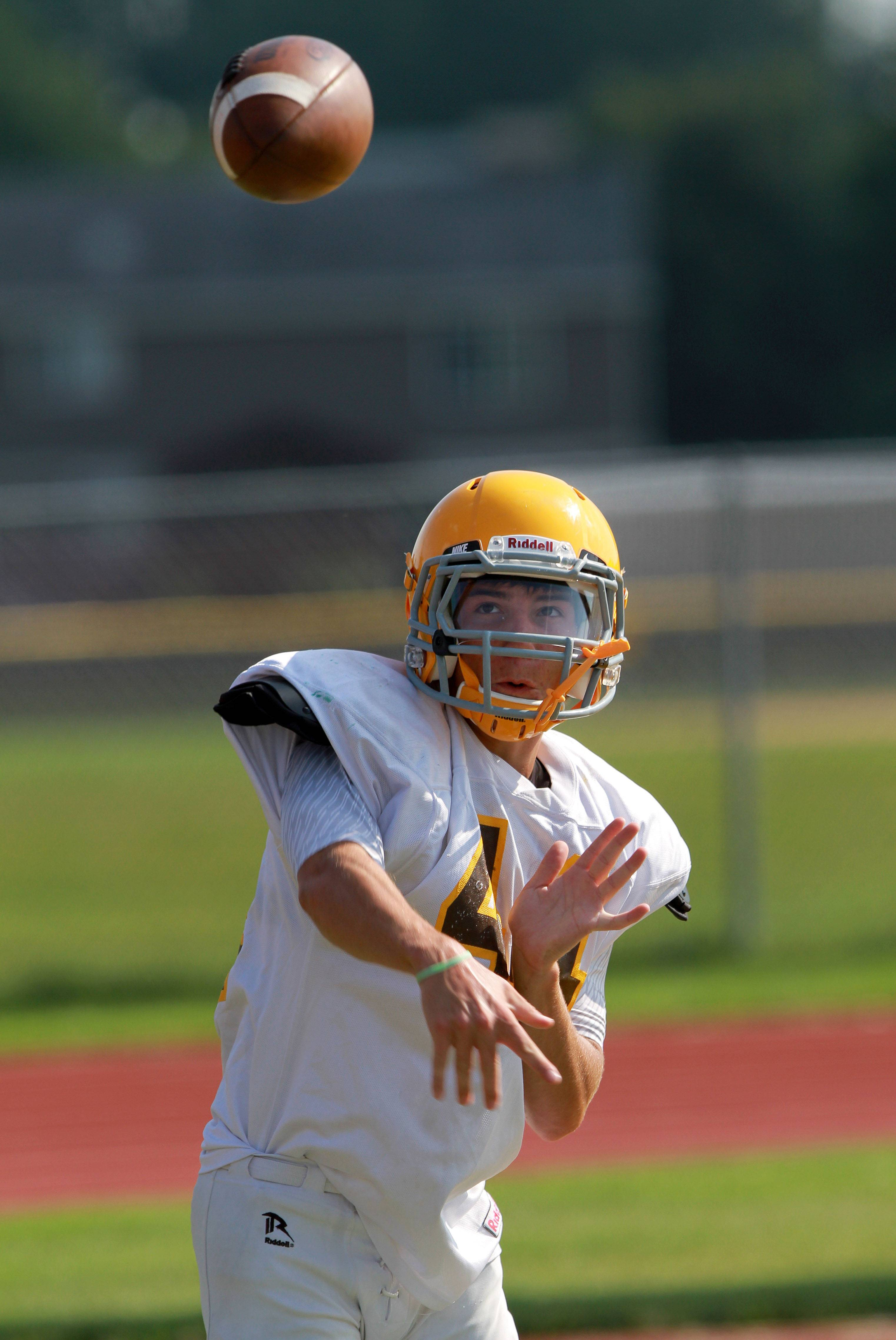 QB Michael Huiras throws during football practice Tuesday at Carmel High School in Mundelein.