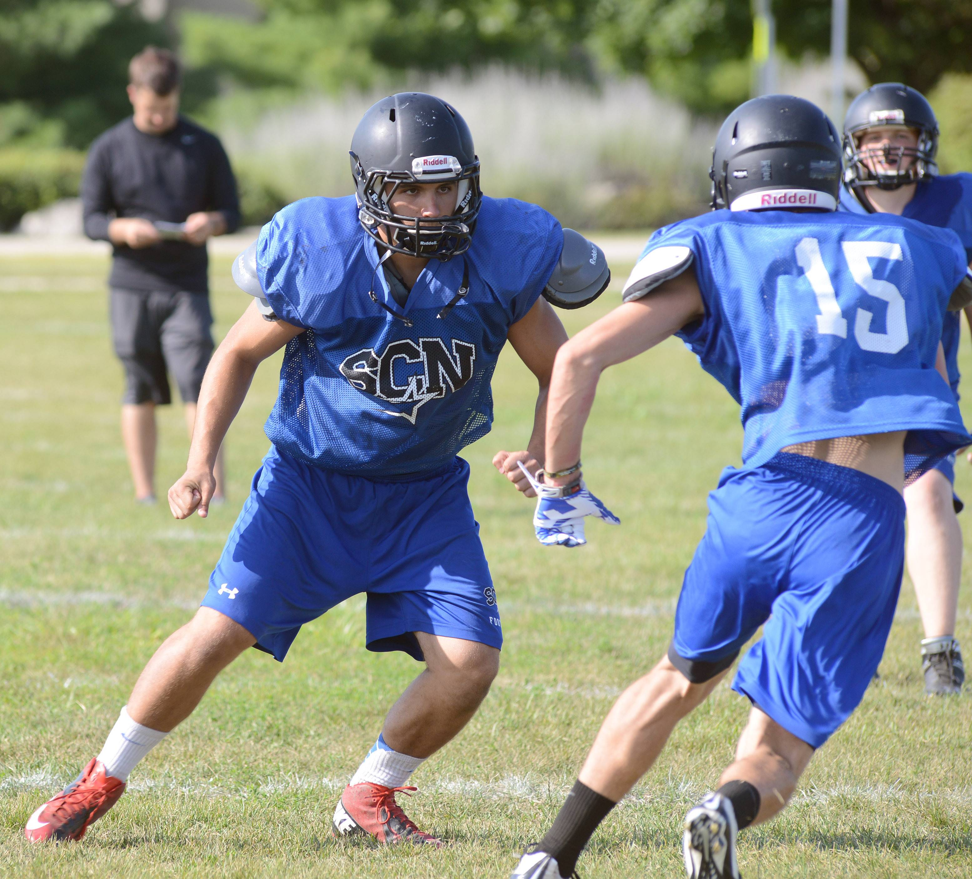 Laura Stoecker/lstoecker@dailyherald.comSt. Charles North junior Dom Sidari, left, during varsity football practice on Friday.