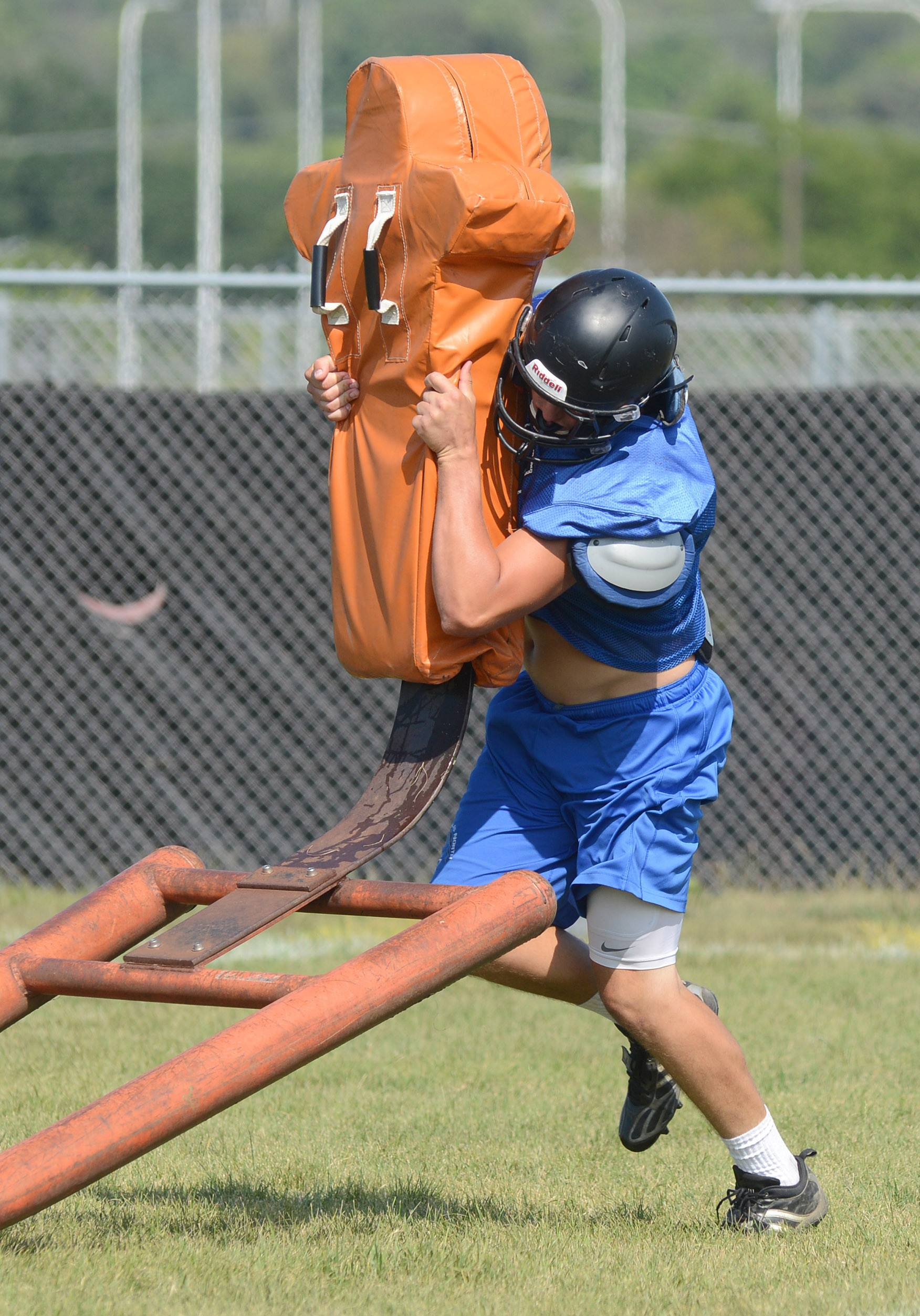 St. Charles North senior Carson Schmitt hits the sled during football practice.
