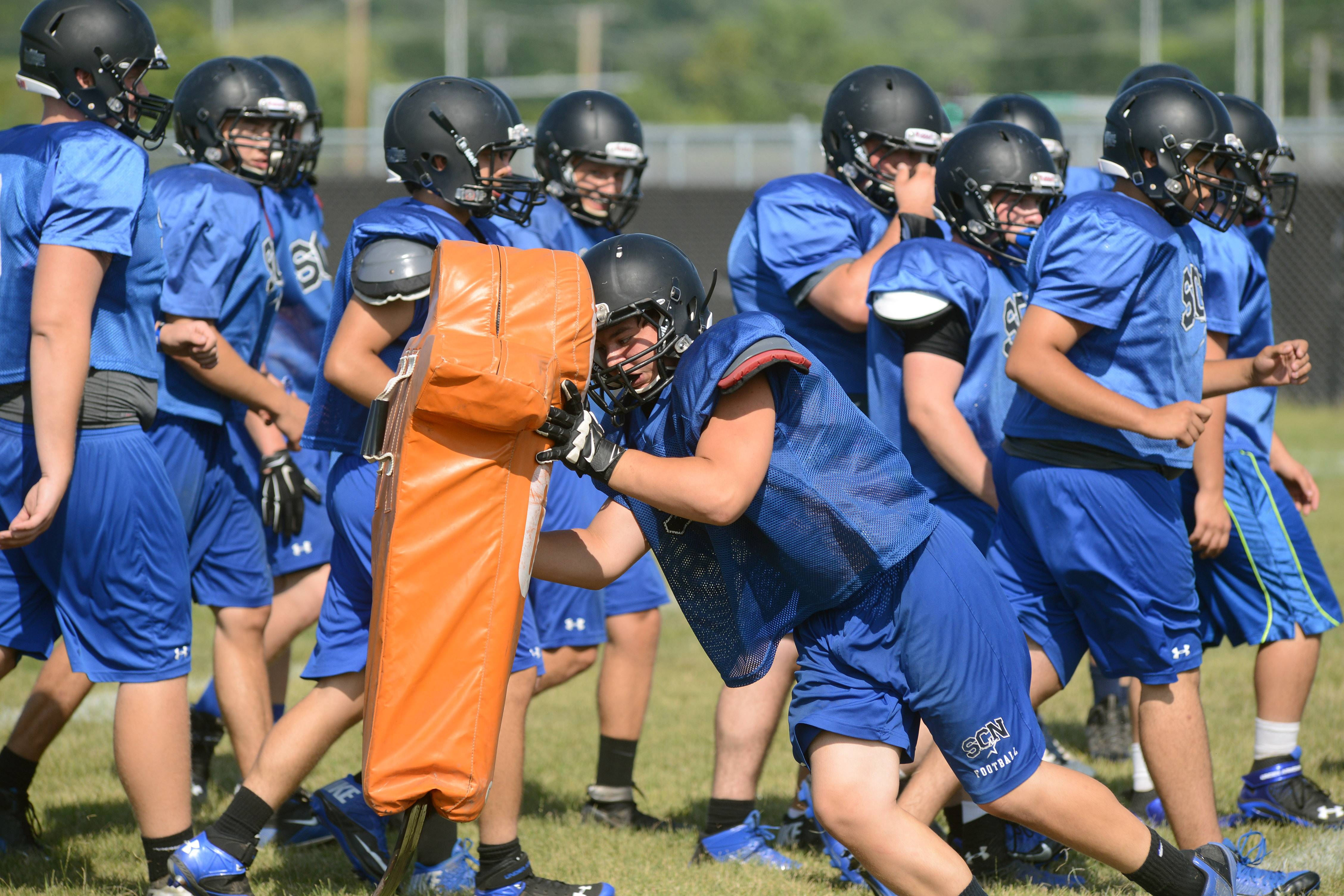 Laura Stoecker/lstoecker@dailyherald.comSt. Charles North varsity football practice hits the sleds on Friday.