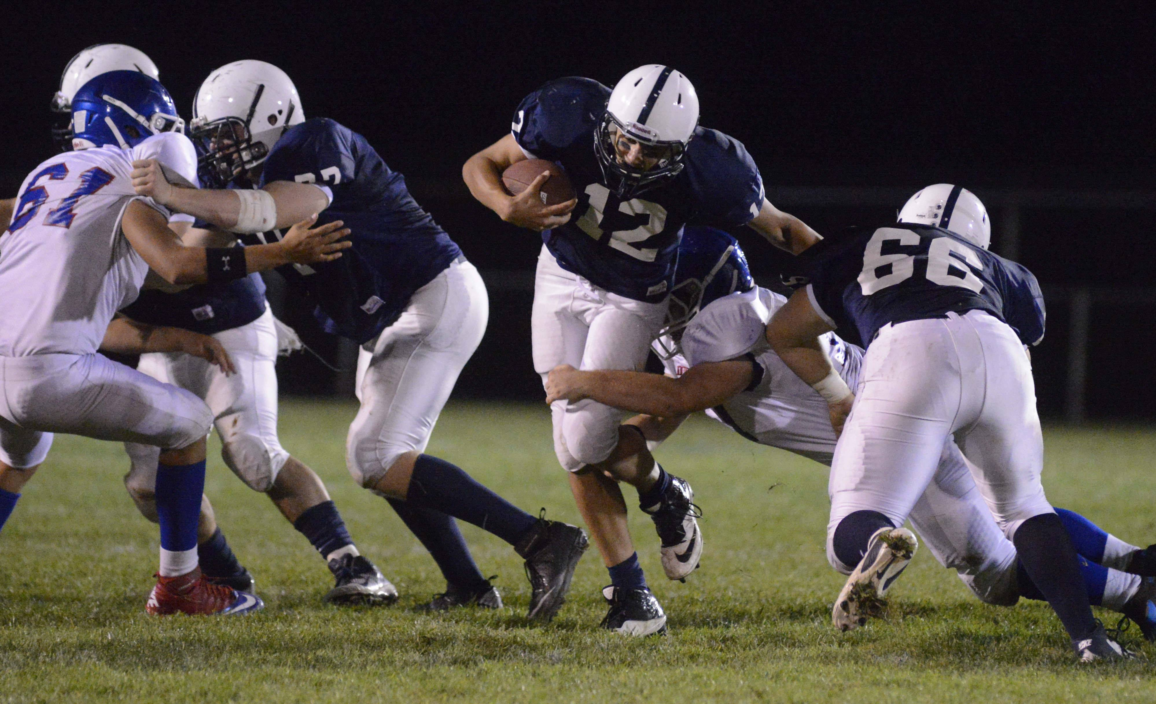 Cary-Grove quarterback Jason Gregoire (12) runs through an open hole against Dundee-Crown last year.