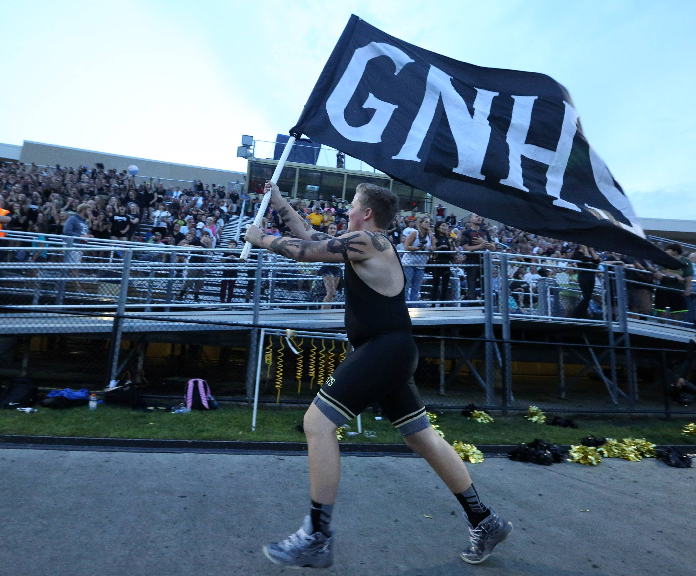 Grayslake North senior Casey Shreiner runs a flag along the sideline to fire up the home fans against visiting Lakes on Friday.