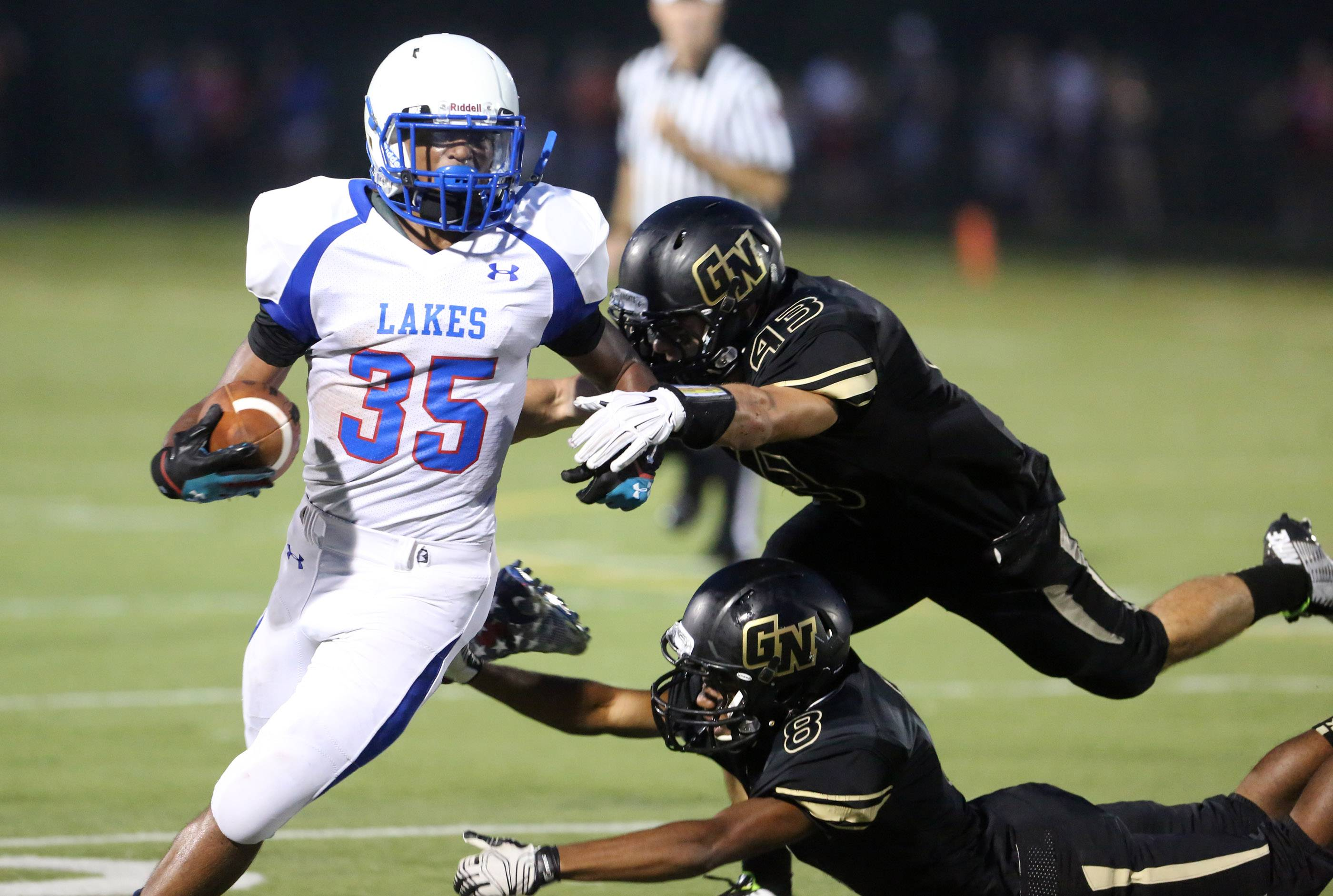 Lakes running back Devyn Cedzidlo slips away from Grayslake defenders Jack McCue, top right, and James King.