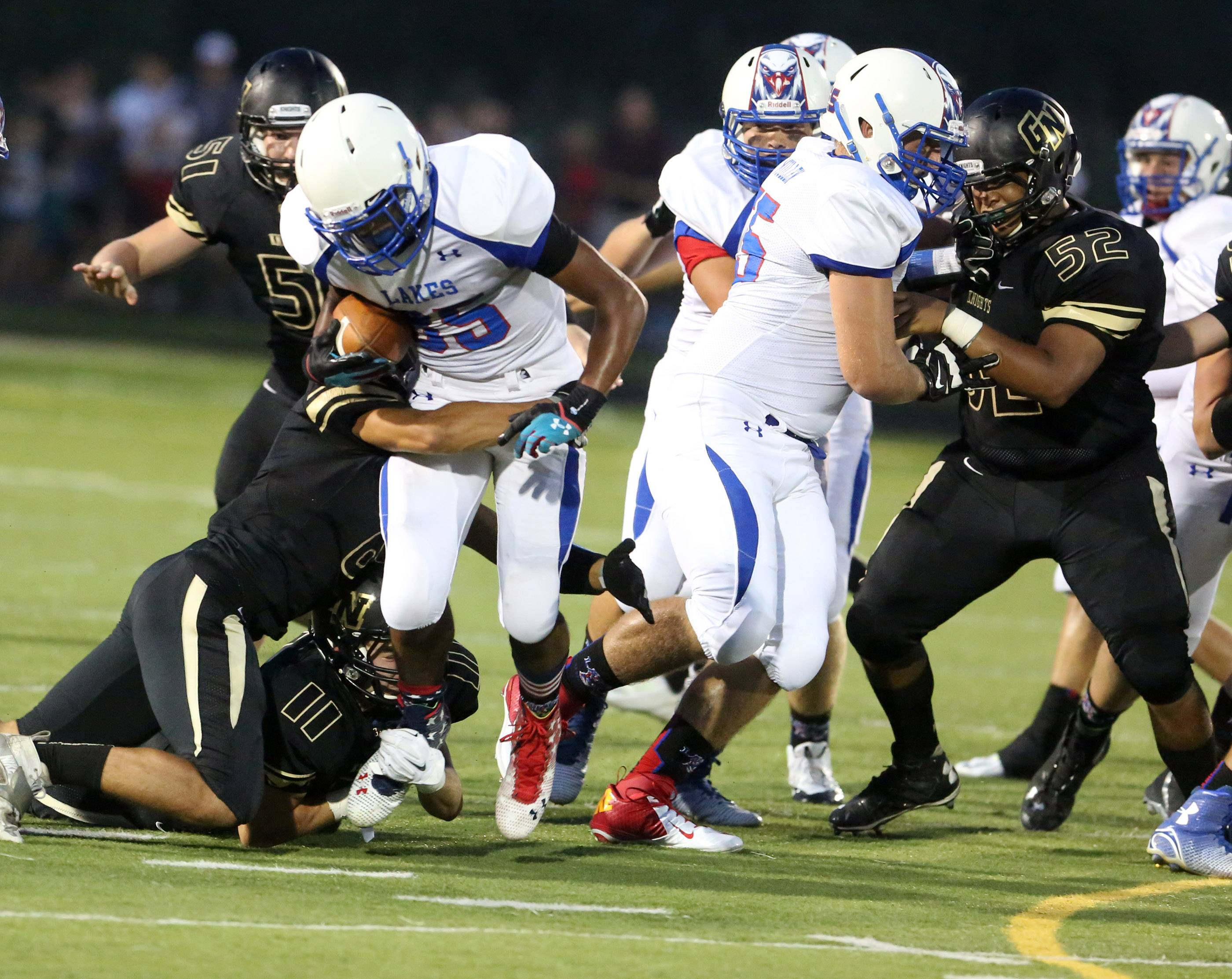 Lakes running back Devyn Cedzidlo is pulled down by Grayslake defenders.