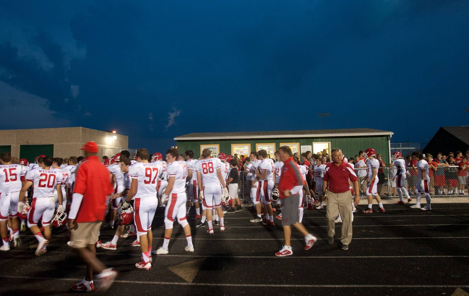 Naperville Central football players and coaches leave the field at Waubonsie Valley. The game was postponed due to lightning.