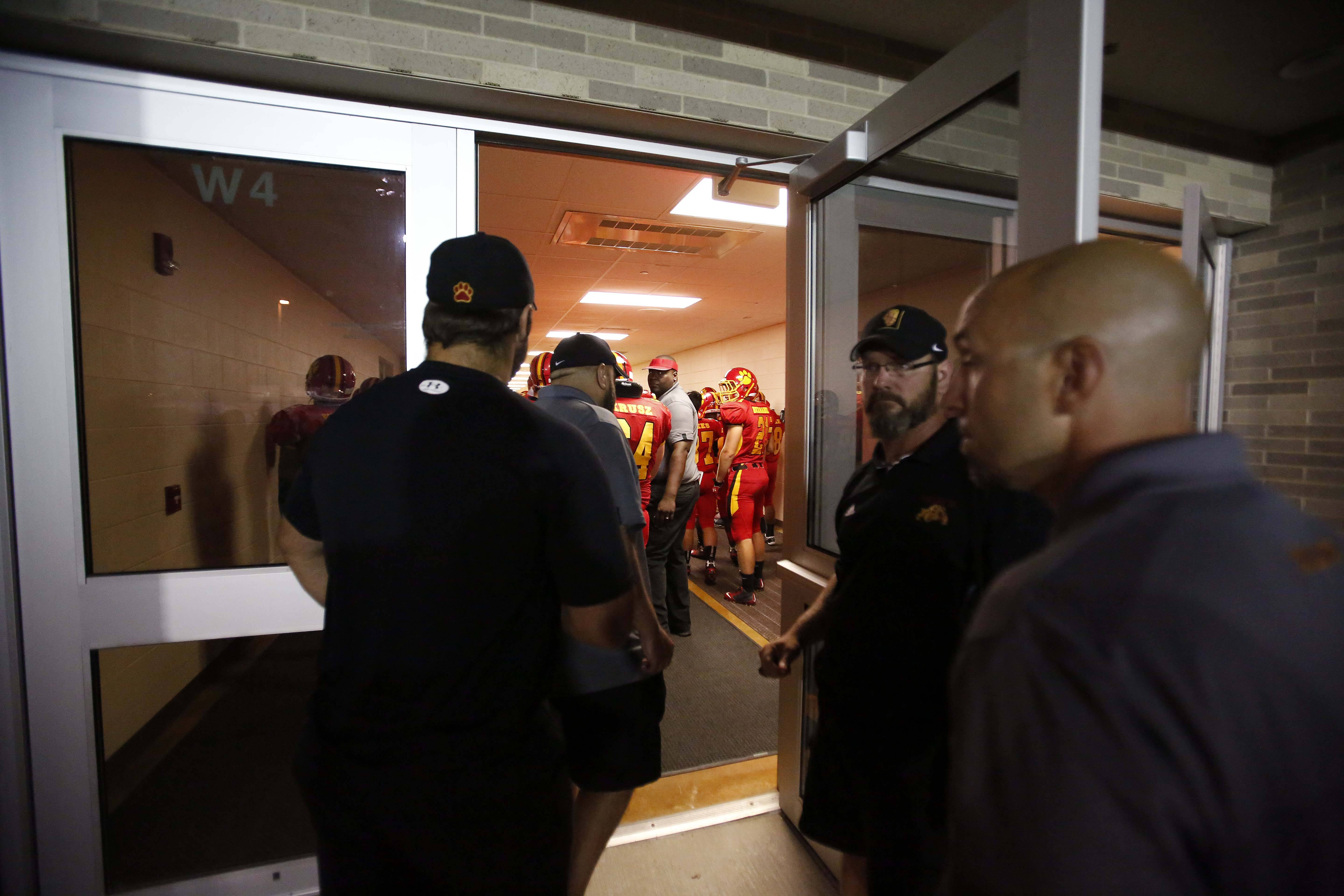 Coaches head in to the locker room after the game was postponed.