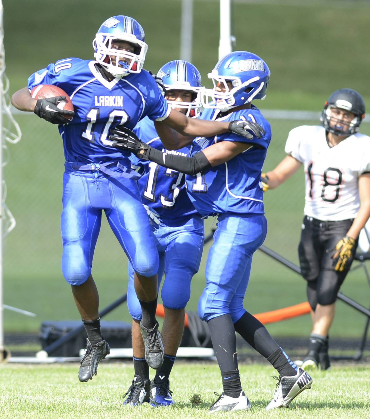 Larkin's Deshawn Steward (10) celebrates a touchdown after scooping up a teammate's fumble against McHenry Saturday at Memorial Field in Elgin.