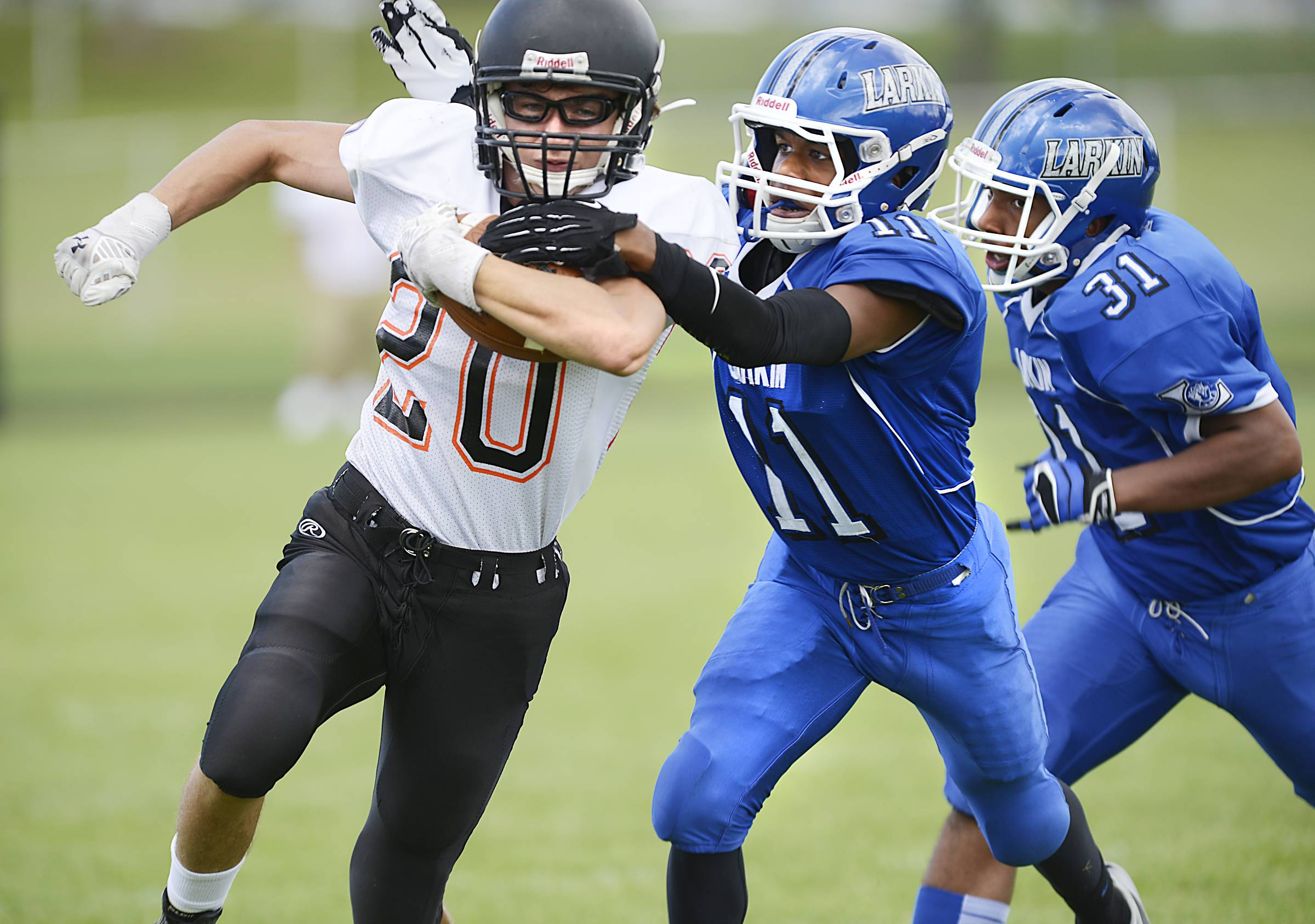 Larkin's AJ Hunter grabs McHenry's Giovanni Purpura as teammate Jared Richardson follows Saturday at Memorial Field in Elgin.