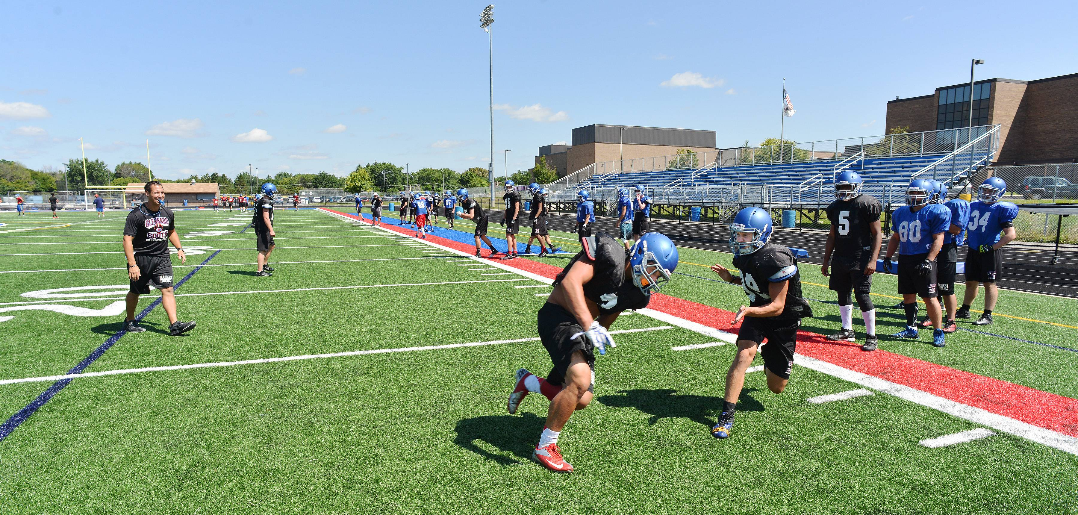 Scott Sanders/ssanders@dailyherald.com ¬ Glenbard South varsity football team works out Thursday morning. Running drills