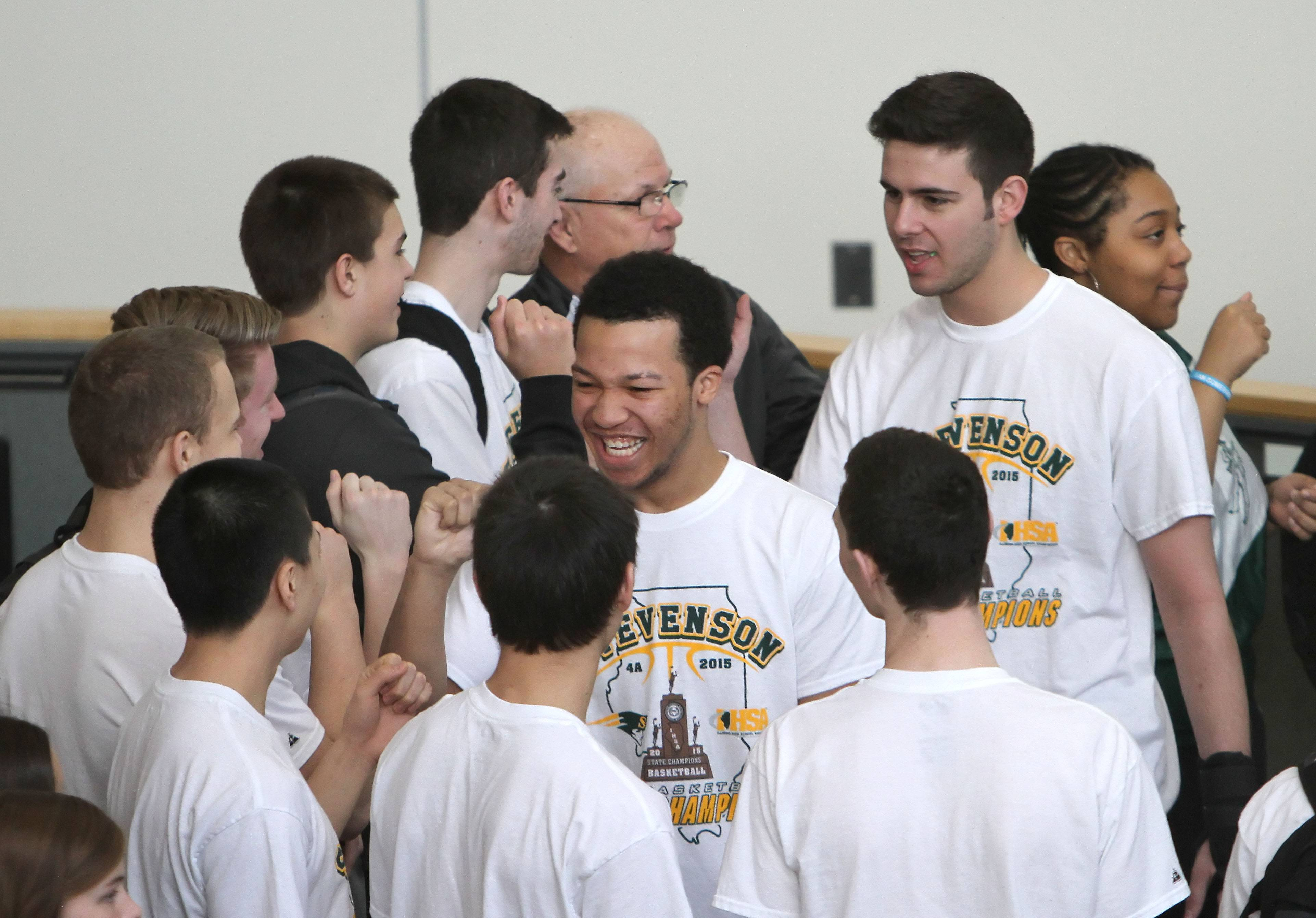 Stevenson High School's Jalen Brunson, left, and Parker Nichols high-five fellow players after being announced as students, staff and community members gathered Thursday to celebrate the boys basketball Class 4A state title in the forum at the Lincolnshire school.