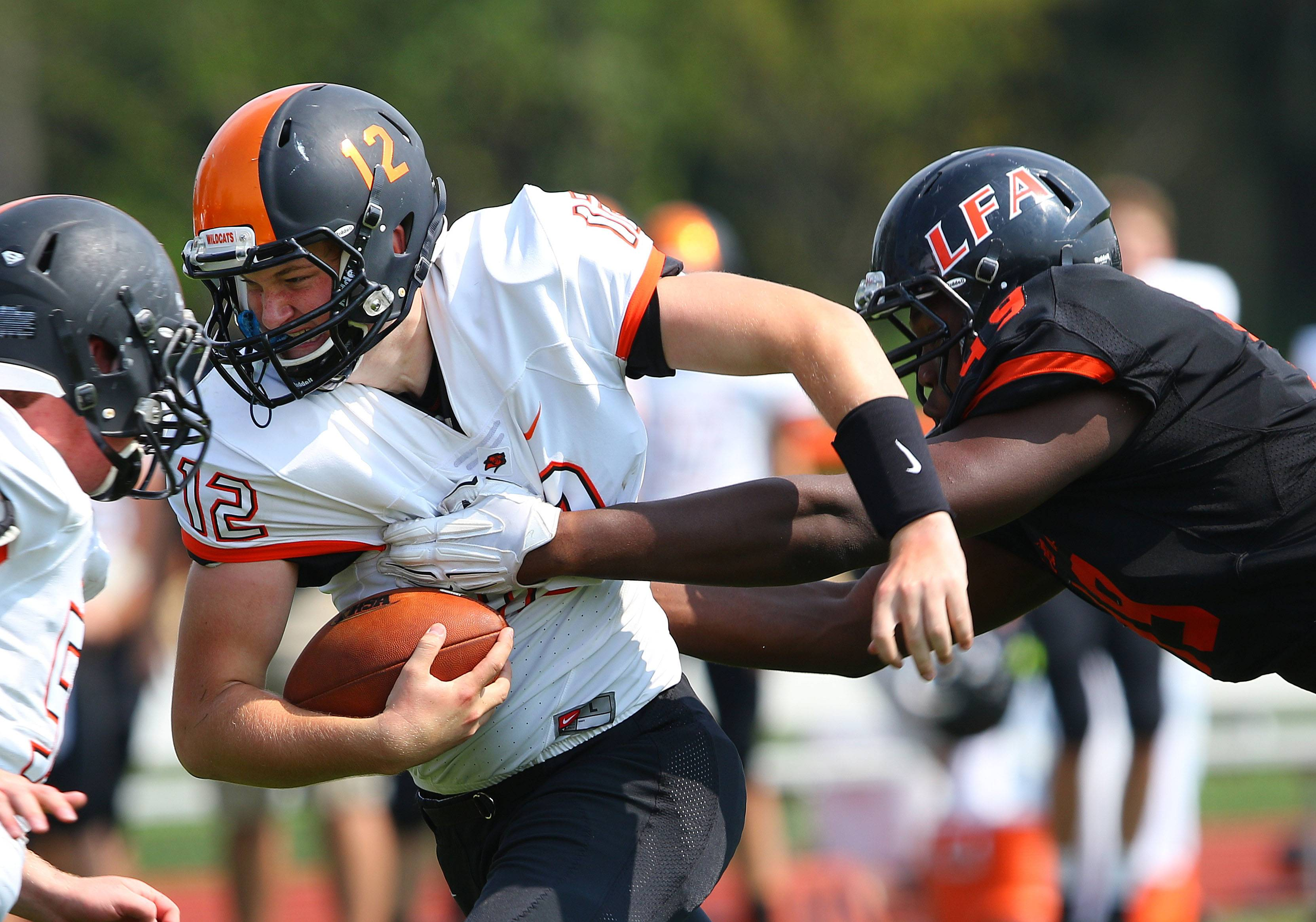 Libertyville QB Mike Schaffer, left, tries to escape the grasp of Lake Forest Academy's Daniel Joseph on Saturday in Lake Forest.