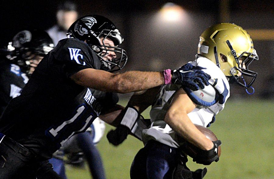 Kirkland Hiawatha's Braden Watson, right, is tracked down by Westminster Christian's Markus Grasemann, left, in Elgin on Friday night.