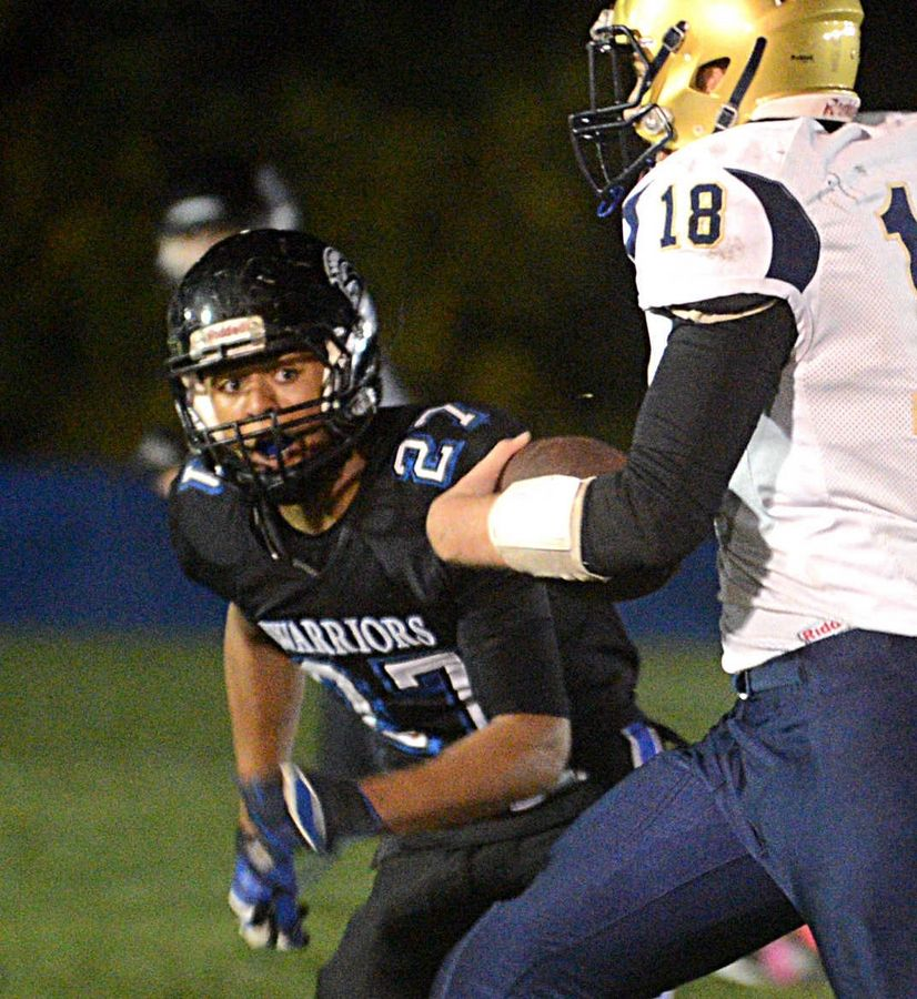 Kirkland Hiawatha quarterback Evan Williams is tracked by Westminster Christian's Xavier Brown, left, in Elgin on Friday night.