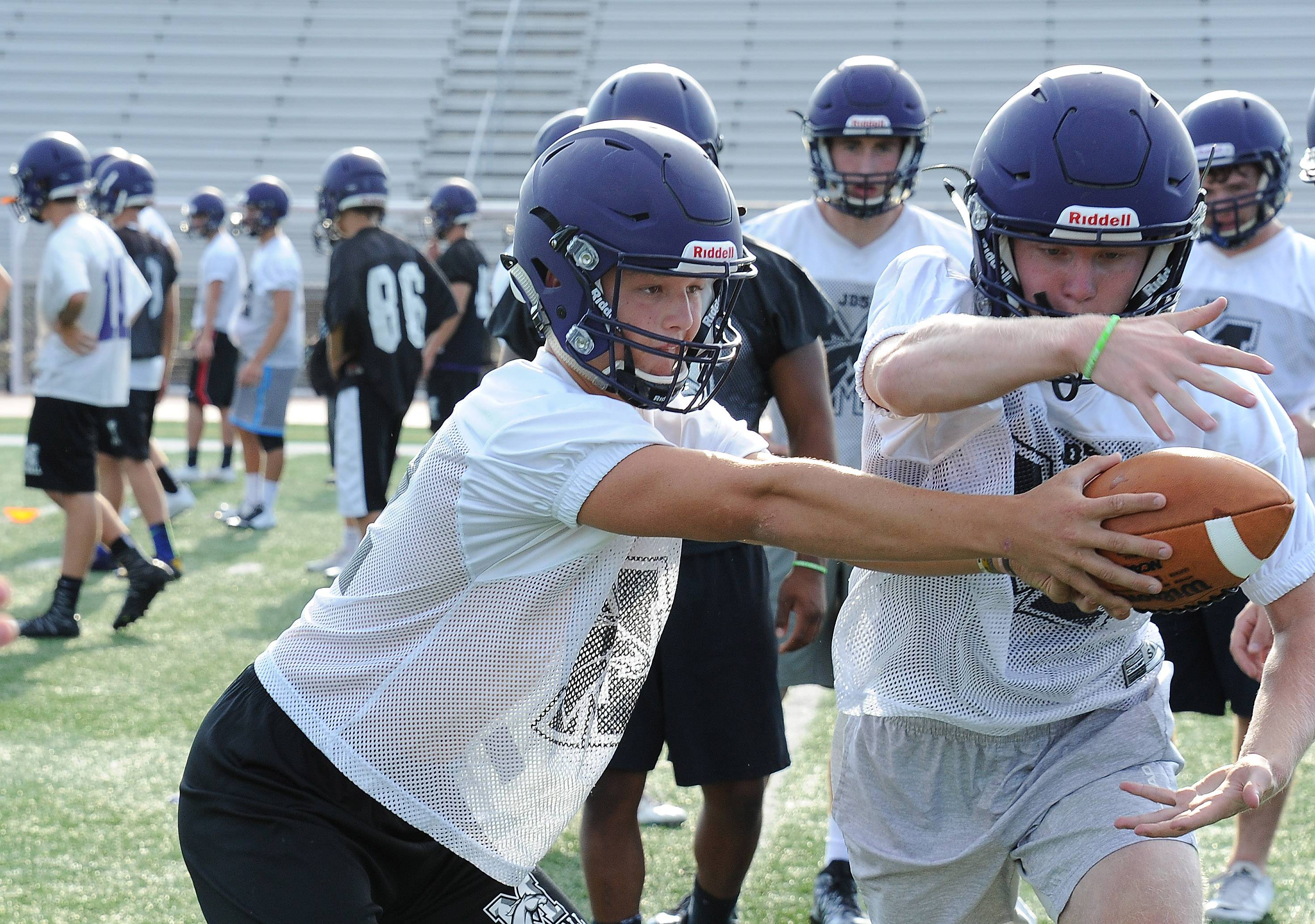 Rolling Meadows quarterback Asher O'Hara hands off to a teammate during the first practice of the season Monday.