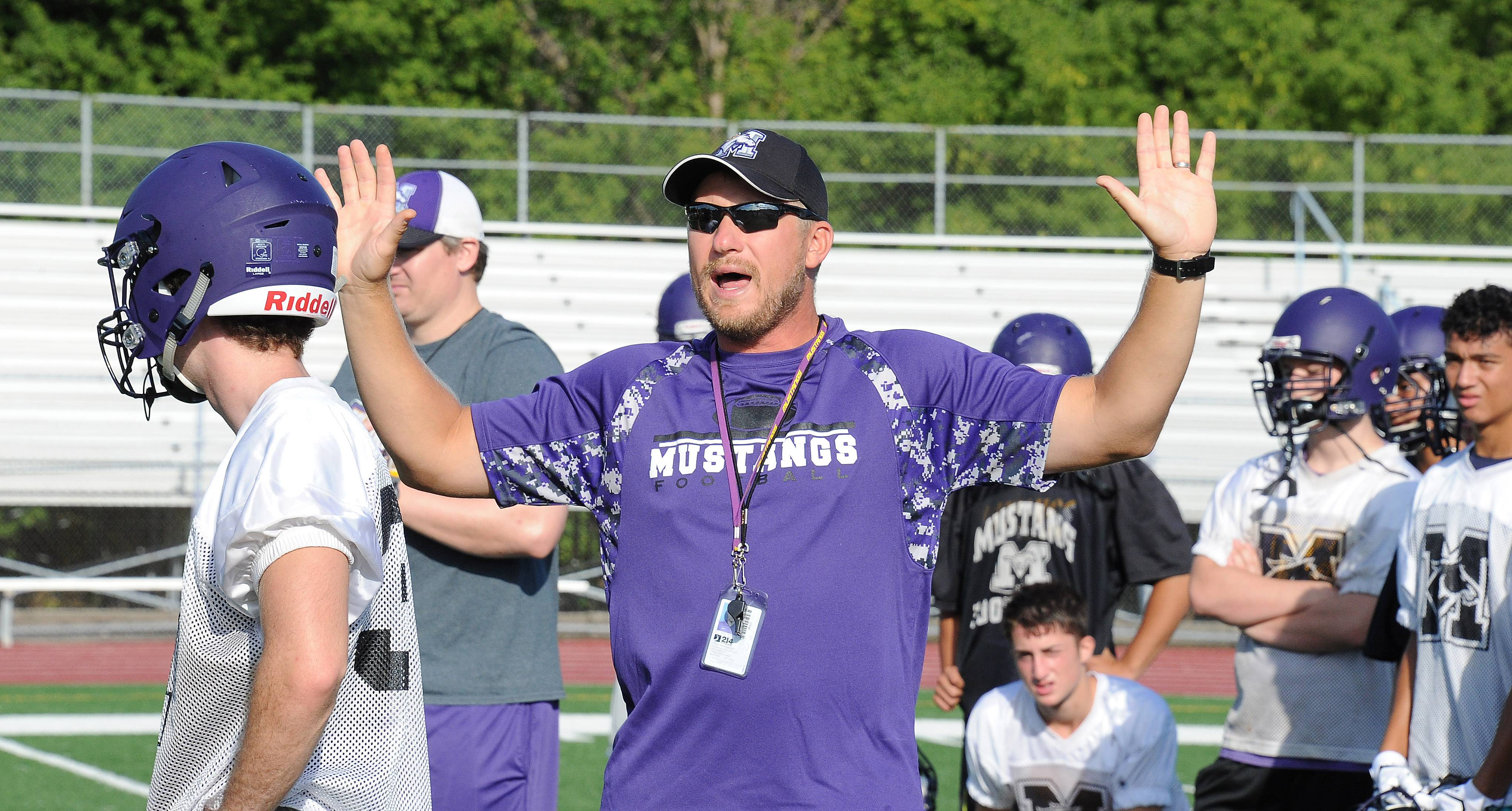 Rolling Meadows coach Matt Mishler speaks to his players on the first day of practice.