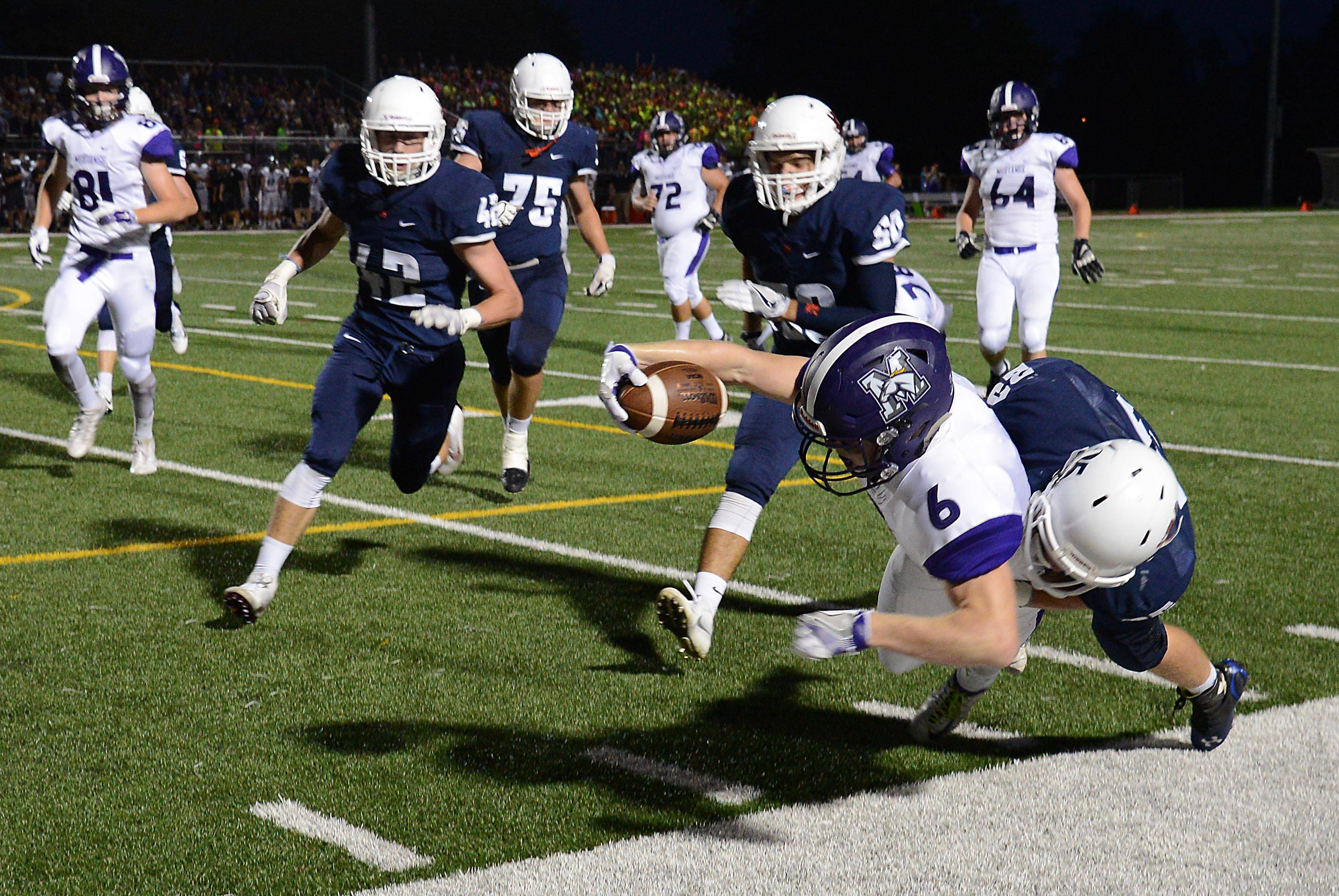 Rolling Meadows' Nick Delporte is brought down at the 3-yard line by St. Viator's Matt Dzuibyk early in the game Friday in Arlington Heights. Delporte then scored on a handoff and scored the 2 extra points on a screen pass.