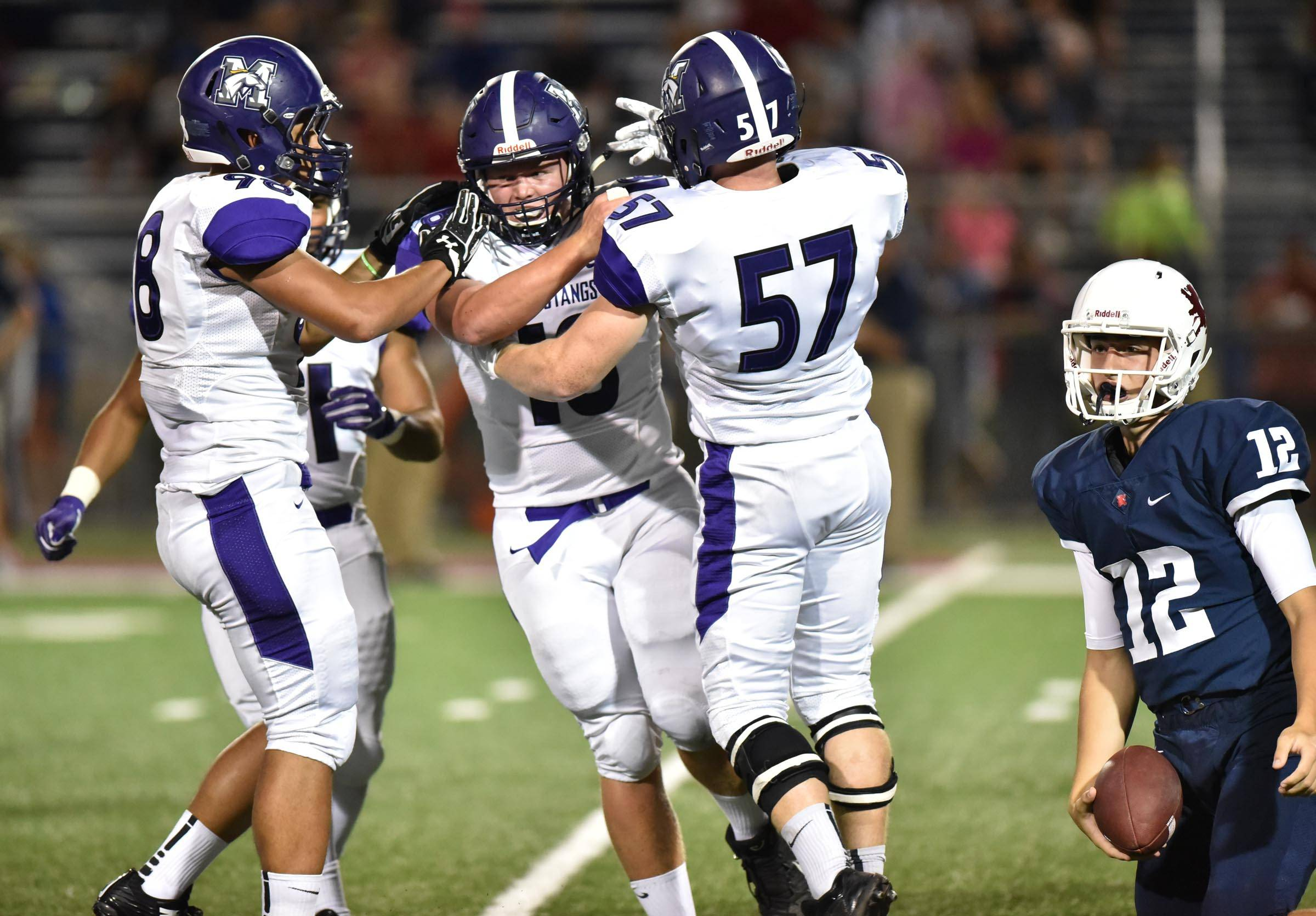 Rolling Meadows' Justin Thompson is met by teammates Luis Robledo and Brian Jacks, right, after his sack of St. Viator quarterback Tom Majerus in the first half Friday in Arlington Heights.