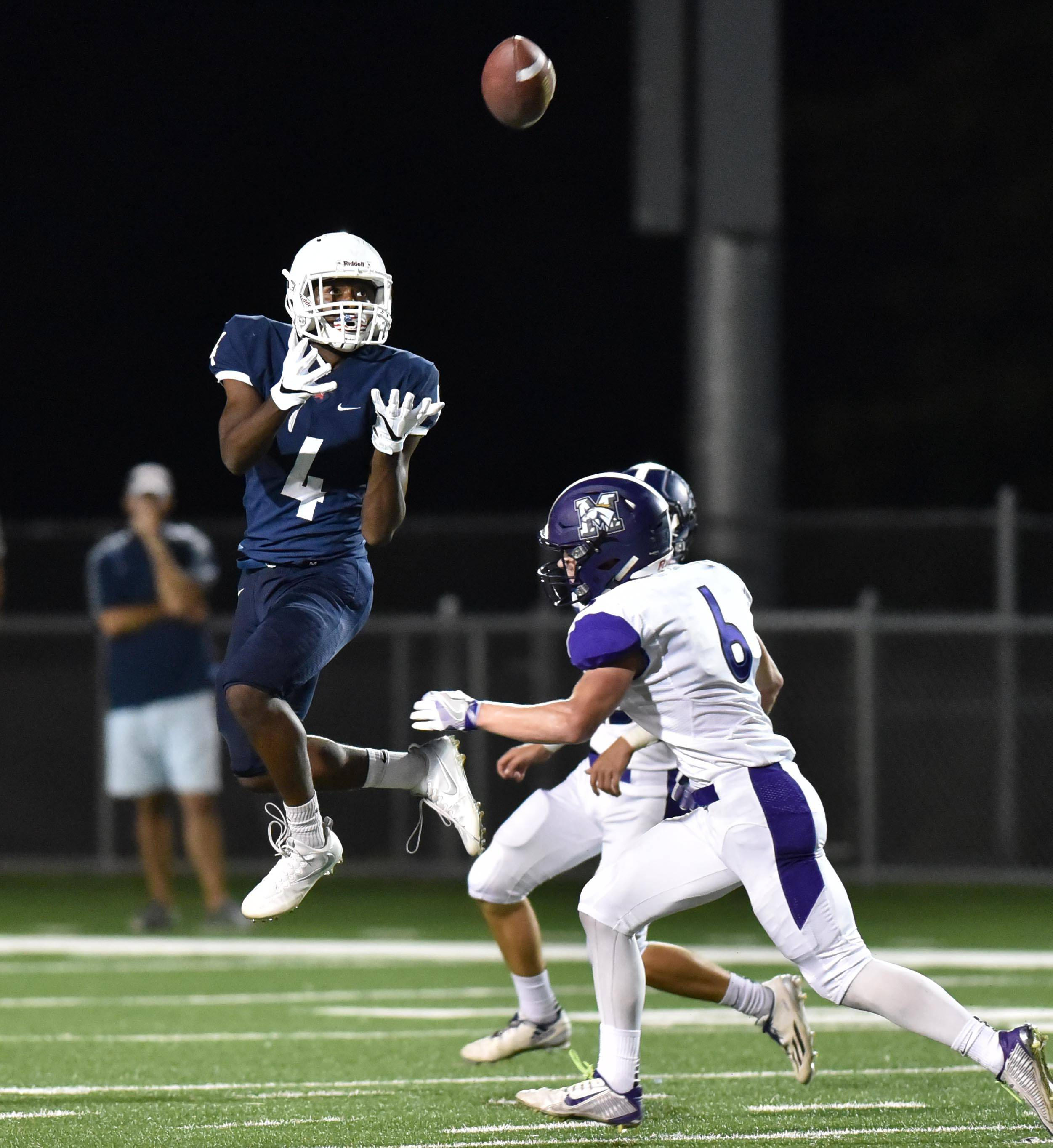 St. Viator's Marc Clark makes a first down catch in the first half as Rolling Meadows' Nick Delporte and Willis Goodwin close in for the tackle Friday in Arlington Heights.