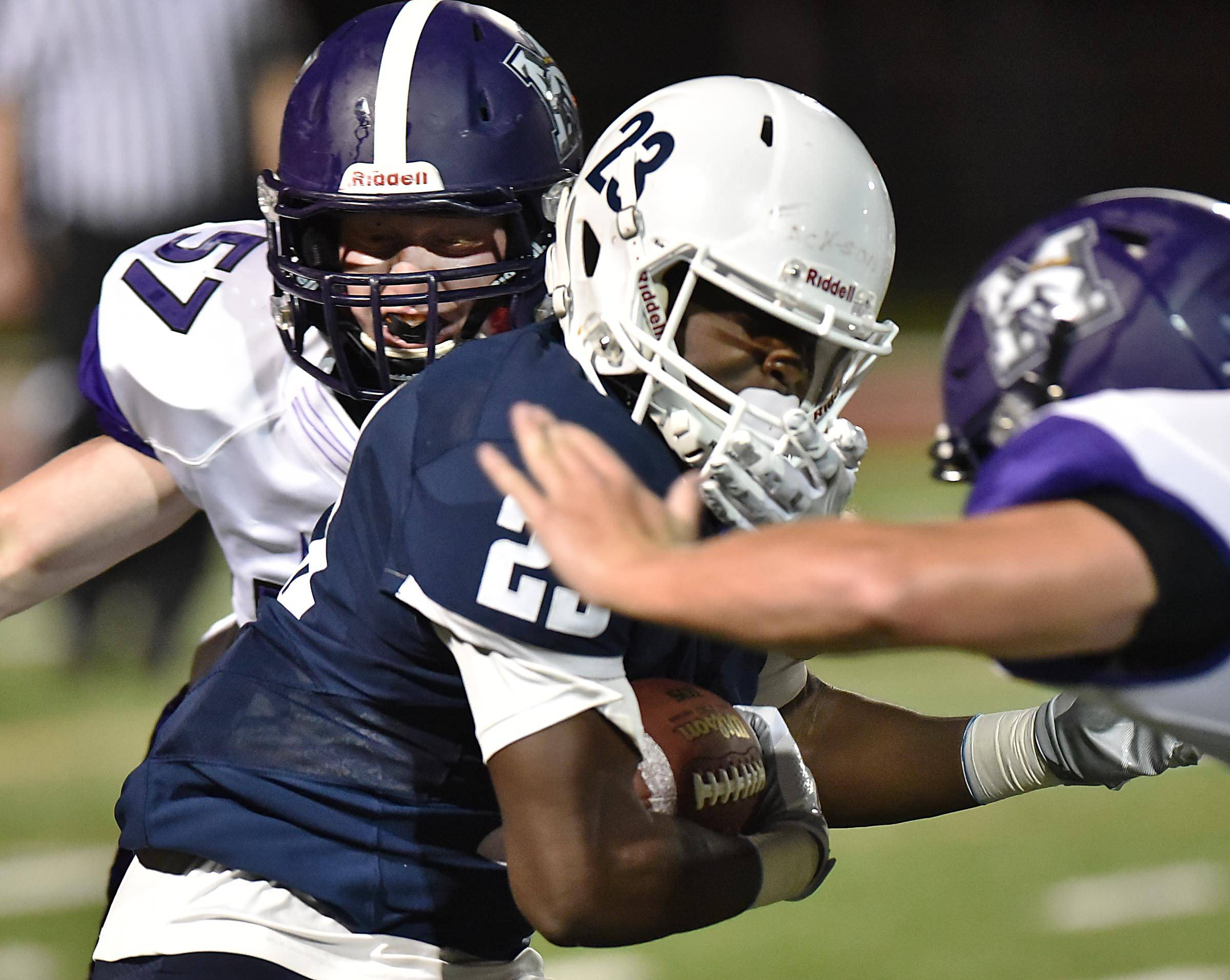 Rolling Meadows' Brian Jacks gets his hand on the face mask of St. Viator's Darreonta Jackson on Friday in Arlington Heights.
