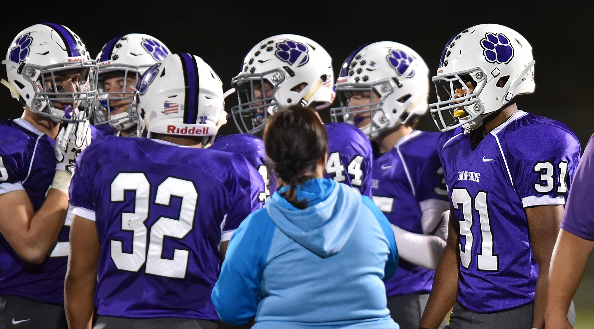 Trevone Woods' interpreter, Laurie Eder, approaches him on the sidelines in a game against Burlington Central Friday in Hampshire.