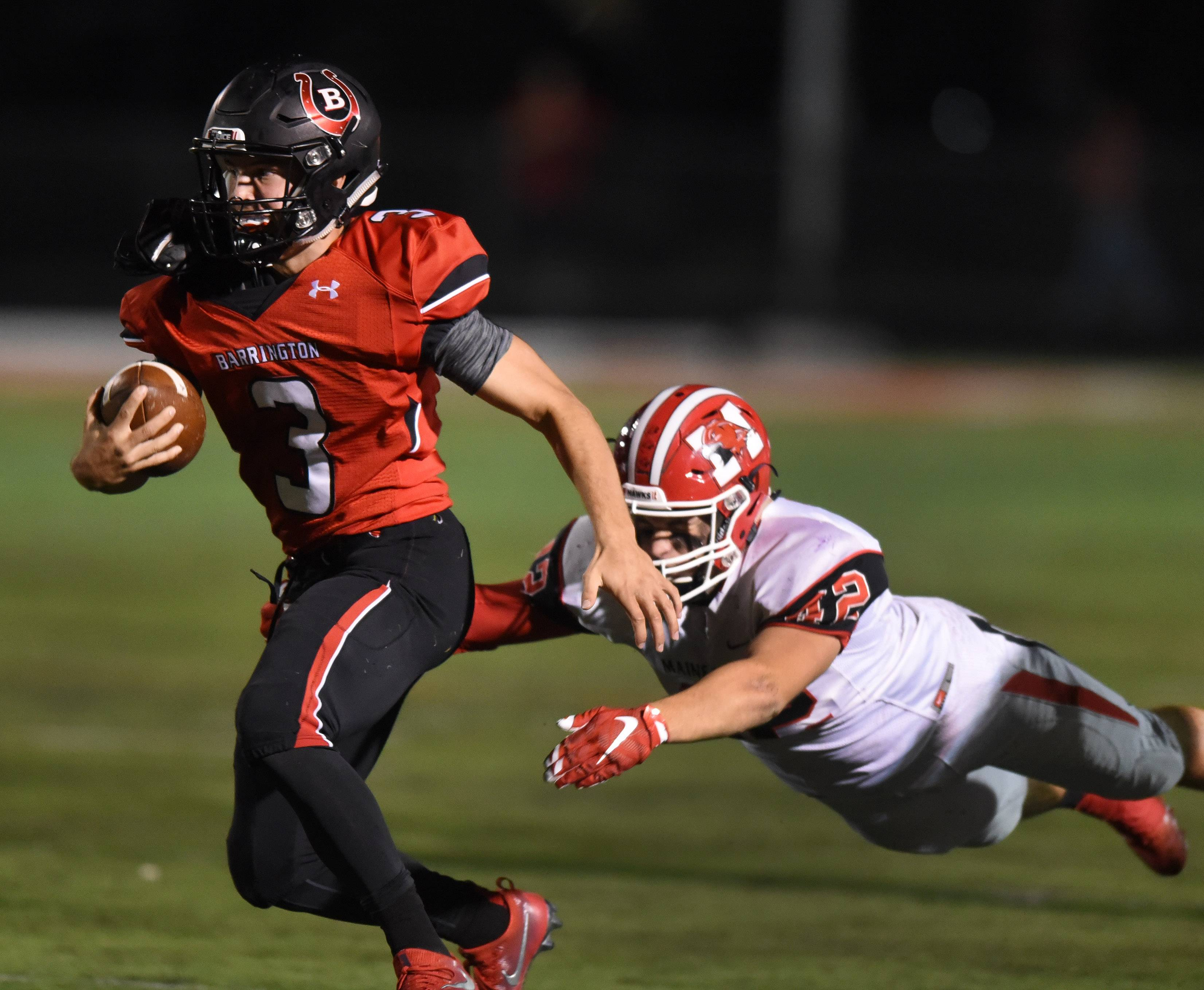 Barrington quarterback Ray Niro carries the ball as Maine South's Michael Pusateri tries to make a tackle during Friday's football game at Barrington.