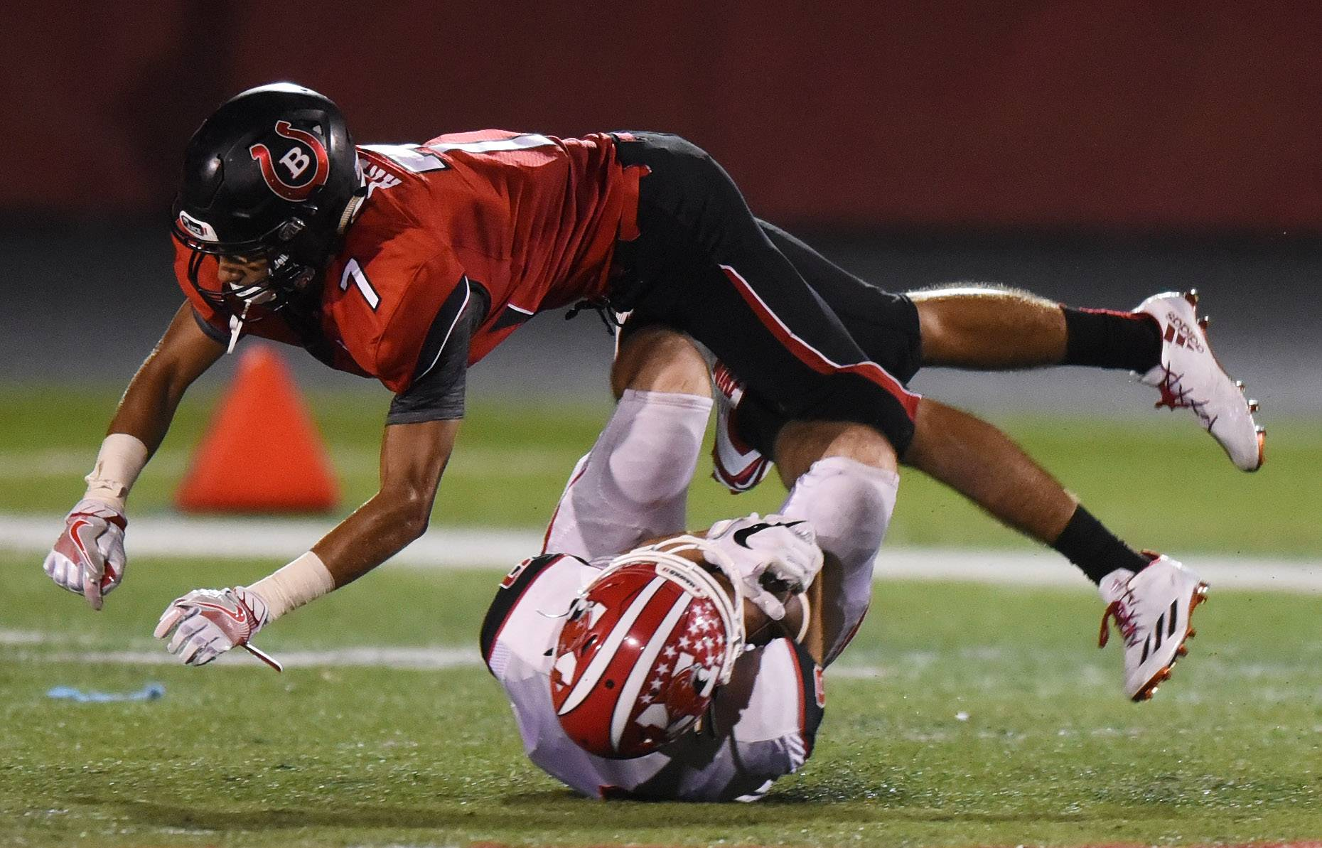 Barrington's Alec Andrea dives over Luke Hinkamp after a catch by the Maine South wide receiver during Friday's football game at Barrington.